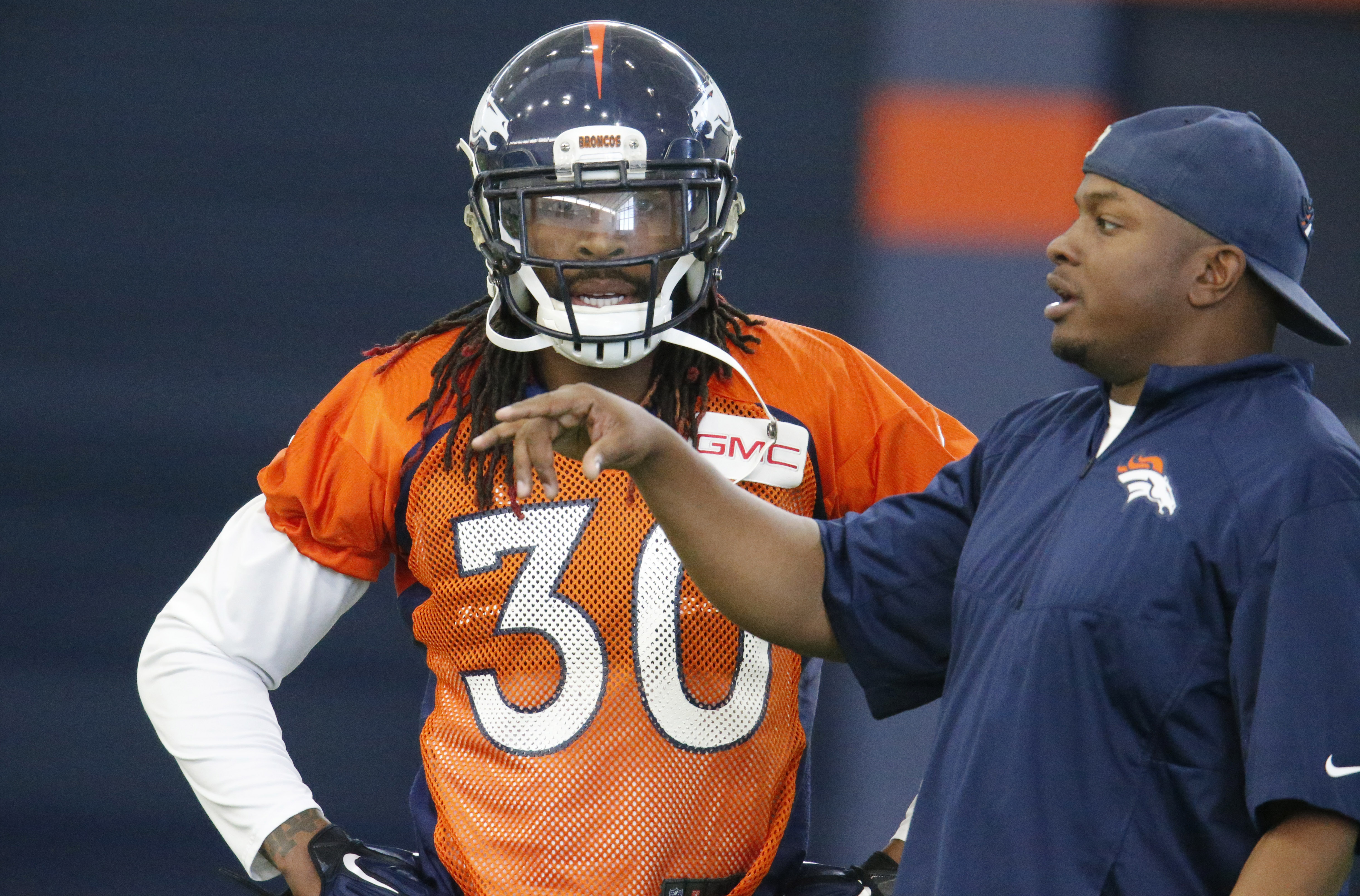 Denver Broncos strong safety David Bruton, left, confers with assistant secondary coach Samson Brown warms up during a practice at the team's headquarters Wednesday, Dec.16, 2015, in Englewood, Colo. (AP Photo/David Zalubowski)