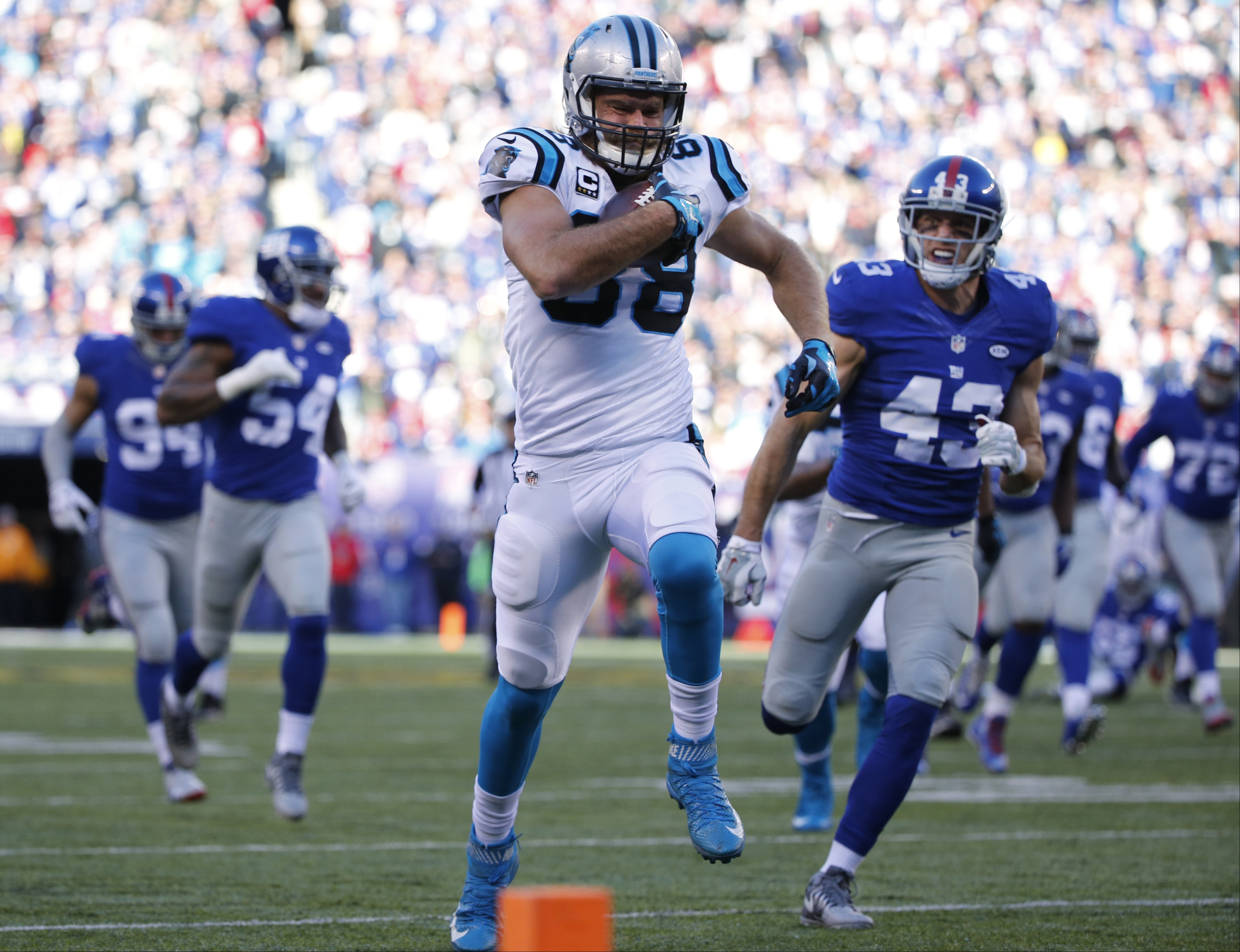Carolina Panthers' Greg Olsen (88) runs away from New York Giants' Craig Dahl (43) for a touchdown during the first half of an NFL football game, Sunday, Dec. 20, 2015, in East Rutherford, N.J. (AP Photo/Kathy Willens)