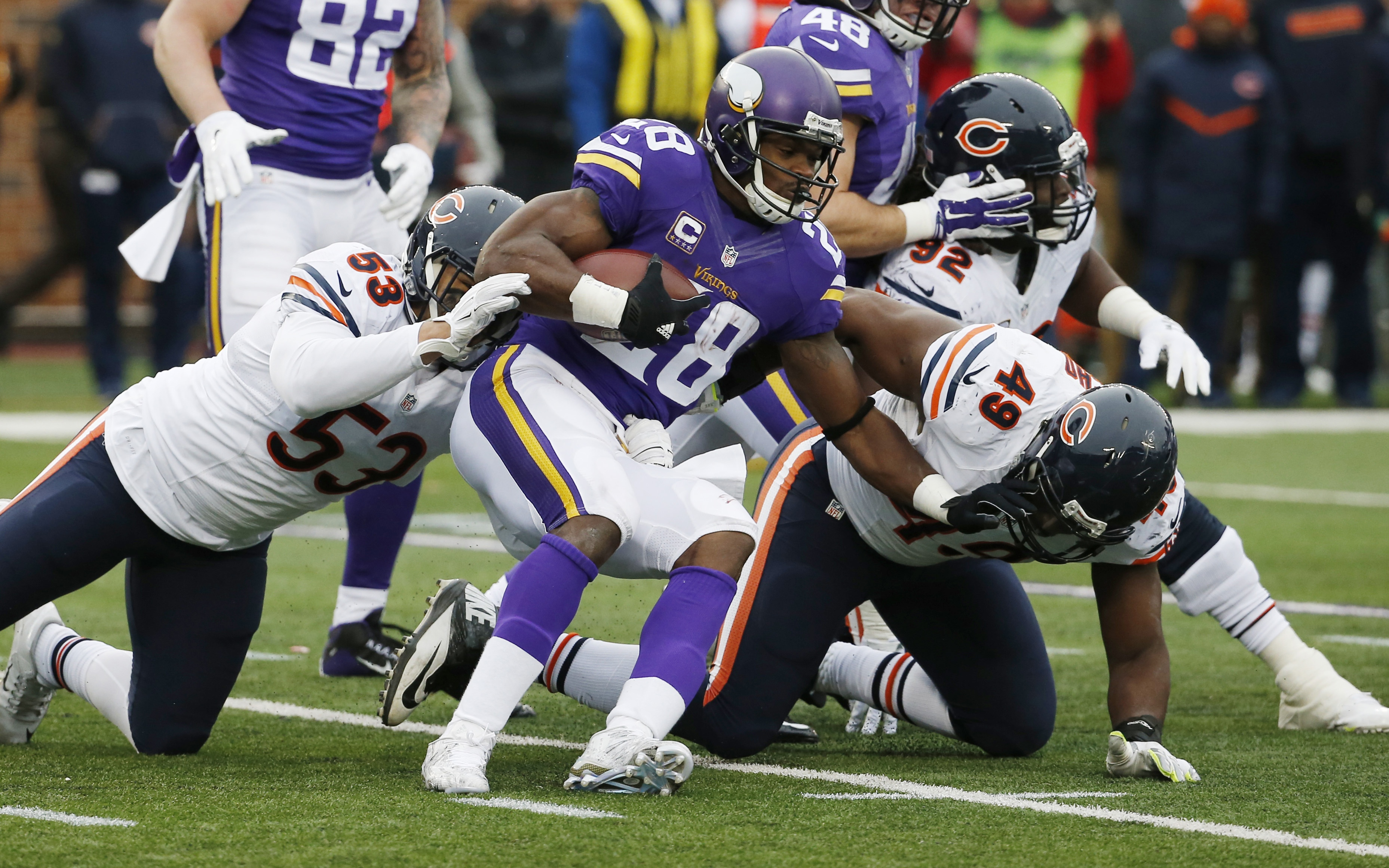 Minnesota Vikings running back Adrian Peterson (28) is stopped by Chicago Bears linebacker John Timu (53) and outside linebacker Sam Acho (49) during the second half of an NFL football game, Sunday, Dec. 20, 2015, in Minneapolis. (AP Photo/Ann Heisenfelt)
