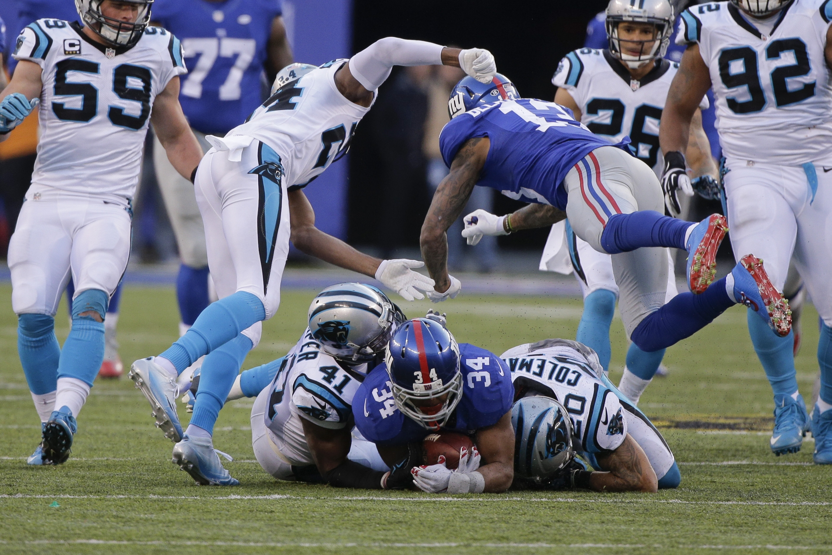 New York Giants' Odell Beckham (13) hits Carolina Panthers' Josh Norman (24) after teammate Shane Vereen (34) is tackled by Kurt Coleman (20) and Roman Harper (41) during the second half of an NFL football game Sunday, Dec. 20, 2015, in East Rutherford, N