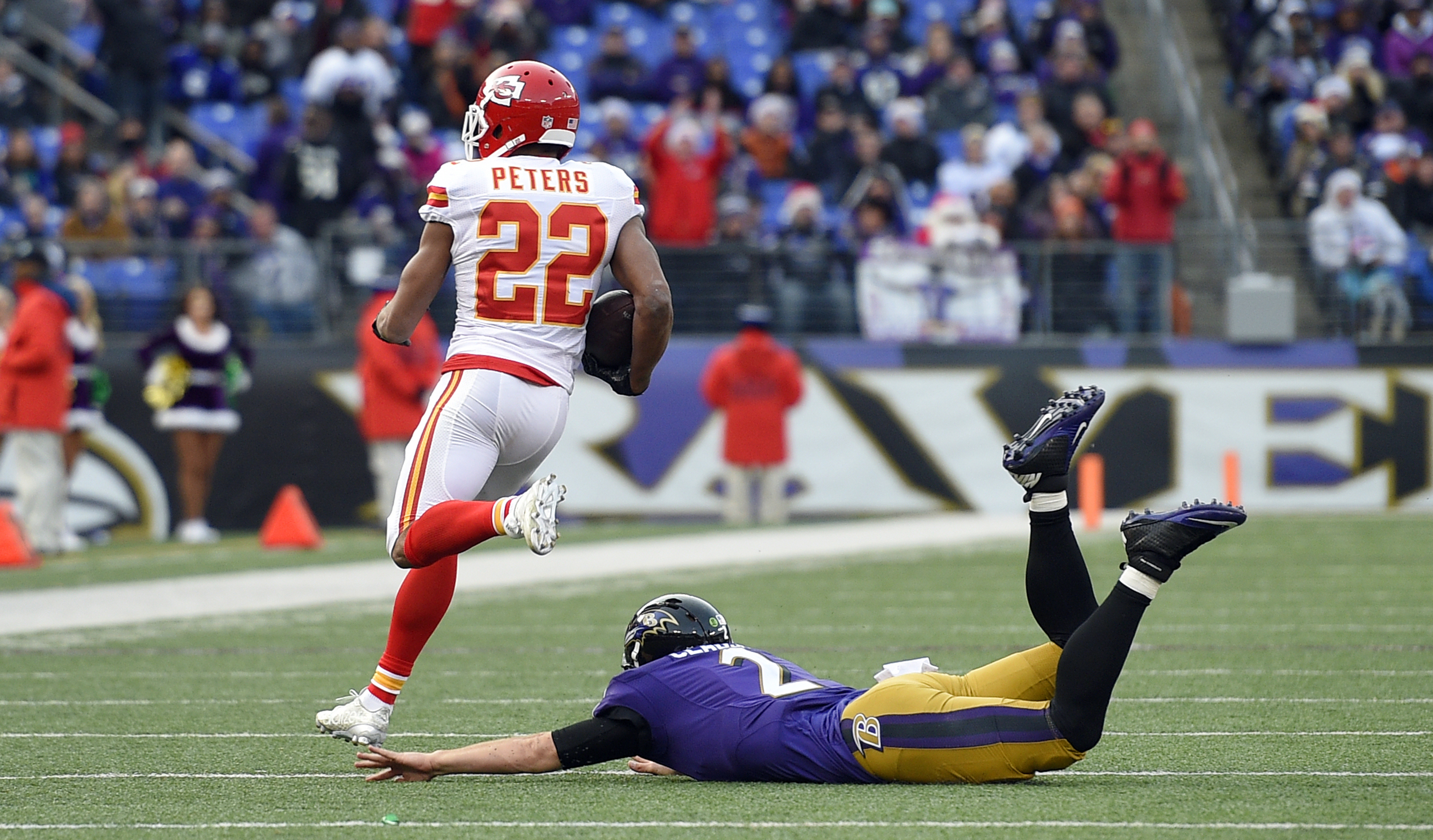 Kansas City Chiefs cornerback Marcus Peters (22) runs past Baltimore Ravens quarterback Jimmy Clausen after intercepting Clausen's pass for a touchdown in the second half of an NFL football game, Sunday, Dec. 20, 2015, in Baltimore. (AP Photo/Nick Wass)