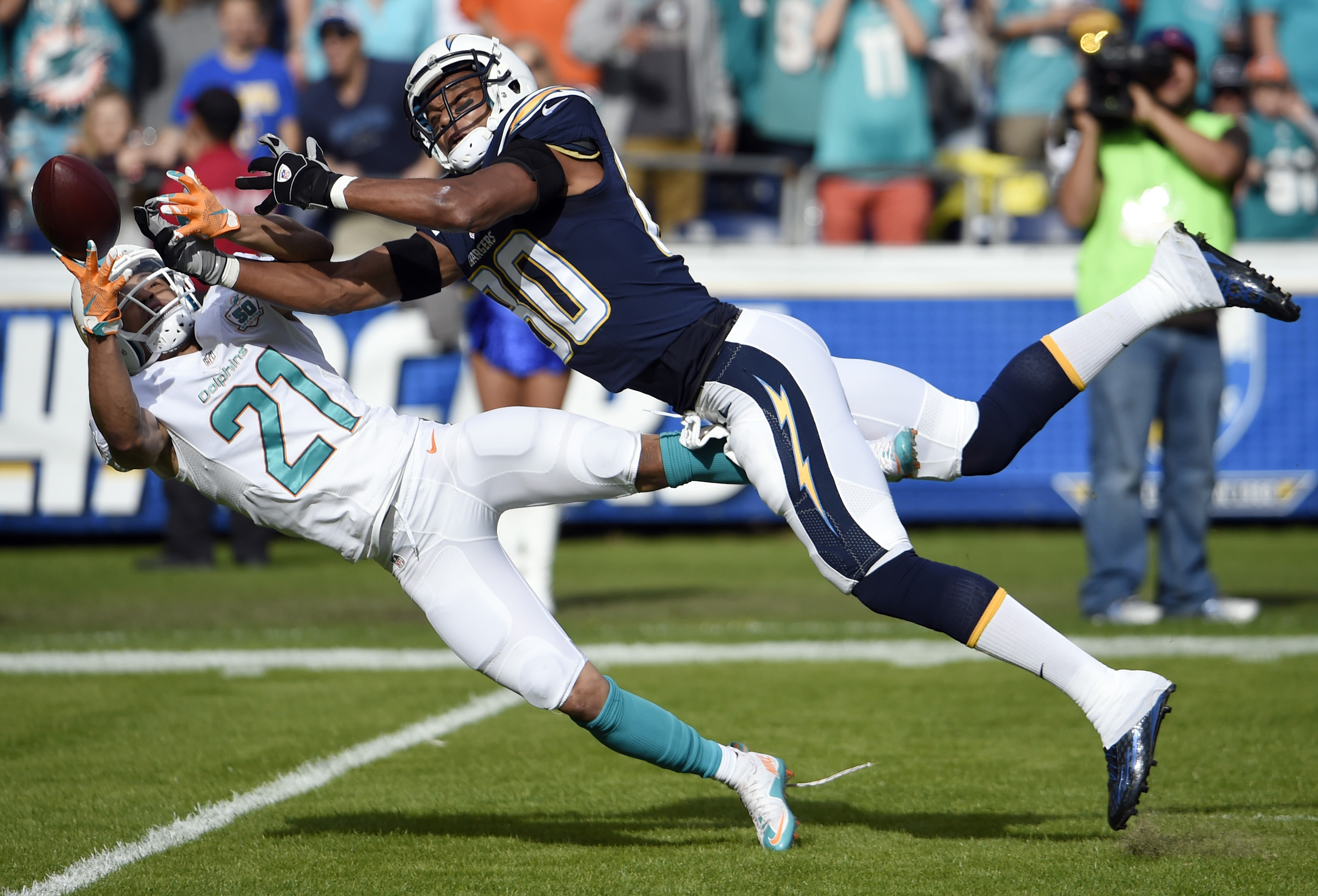 Miami Dolphins cornerback Brent Grimes, left, breaks up a pass intended for San Diego Chargers wide receiver Malcom Floyd during the first half in an NFL football game Sunday, Dec. 20, 2015, in San Diego. (AP Photo/Denis Poroy)