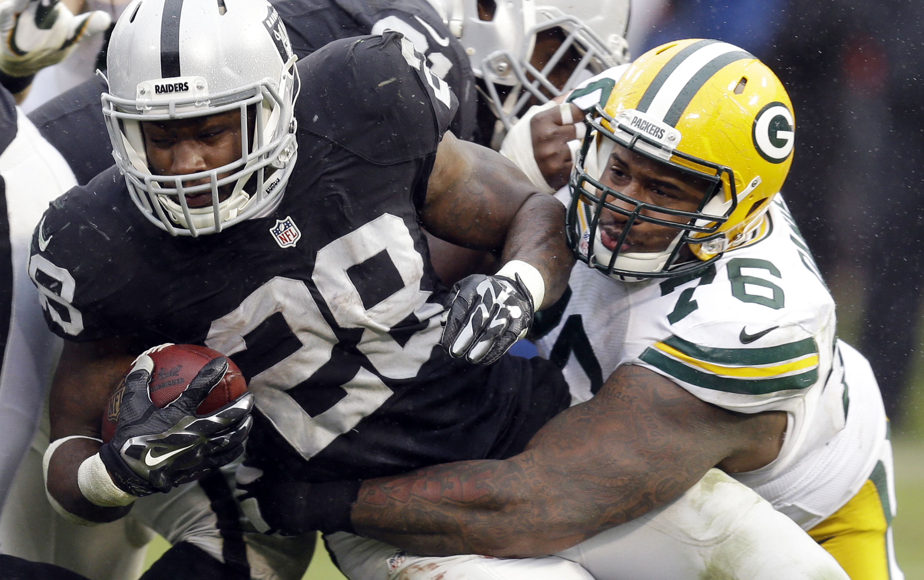 FILE - In this Dec. 20, 2015, file photo, Oakland Raiders running back Latavius Murray (28) is tackled by Green Bay Packers defensive end Mike Daniels (76) during the second half of an NFL football game in Oakland, Calif. With a playoff berth assured, the
