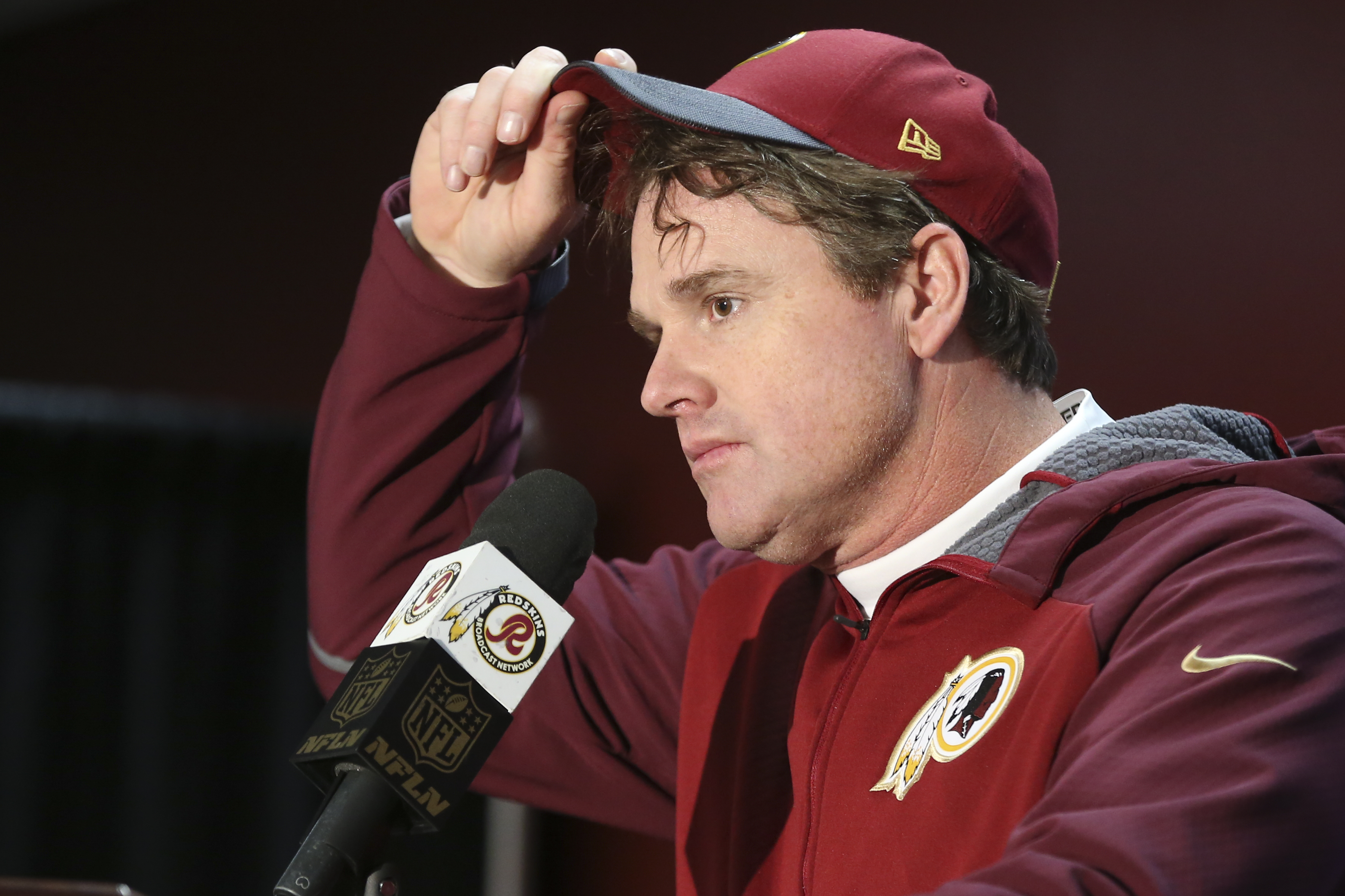 In this Dec. 20, 2015, photo, Washington Redskins head coach Jay Gruden pulls on his cap during a post-game news conference after the NFL football game against the Buffalo Bills in Landover, Md., Sunday, Dec. 20, 2015. The Washington Redskins defeated the