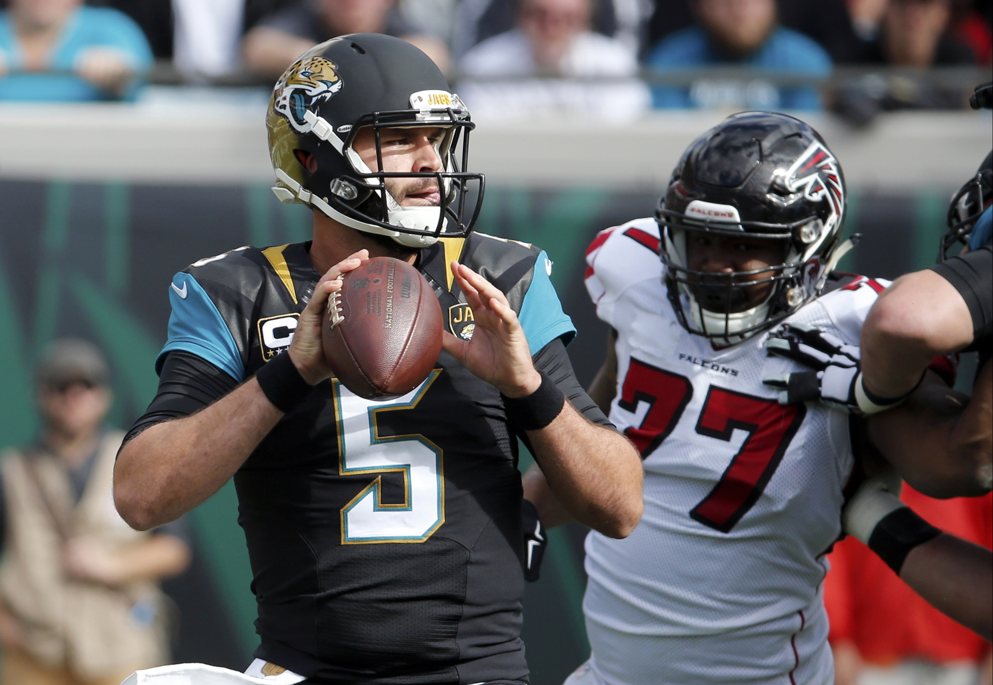 FILE - In this Dec. 20, 2015, file photo, Jacksonville Jaguars quarterback Blake Bortles (5) looks for a receiver as he is pressured by Atlanta Falcons defensive tackle Ra'Shede Hageman (77) during the first half of an NFL football game in Jacksonville, F