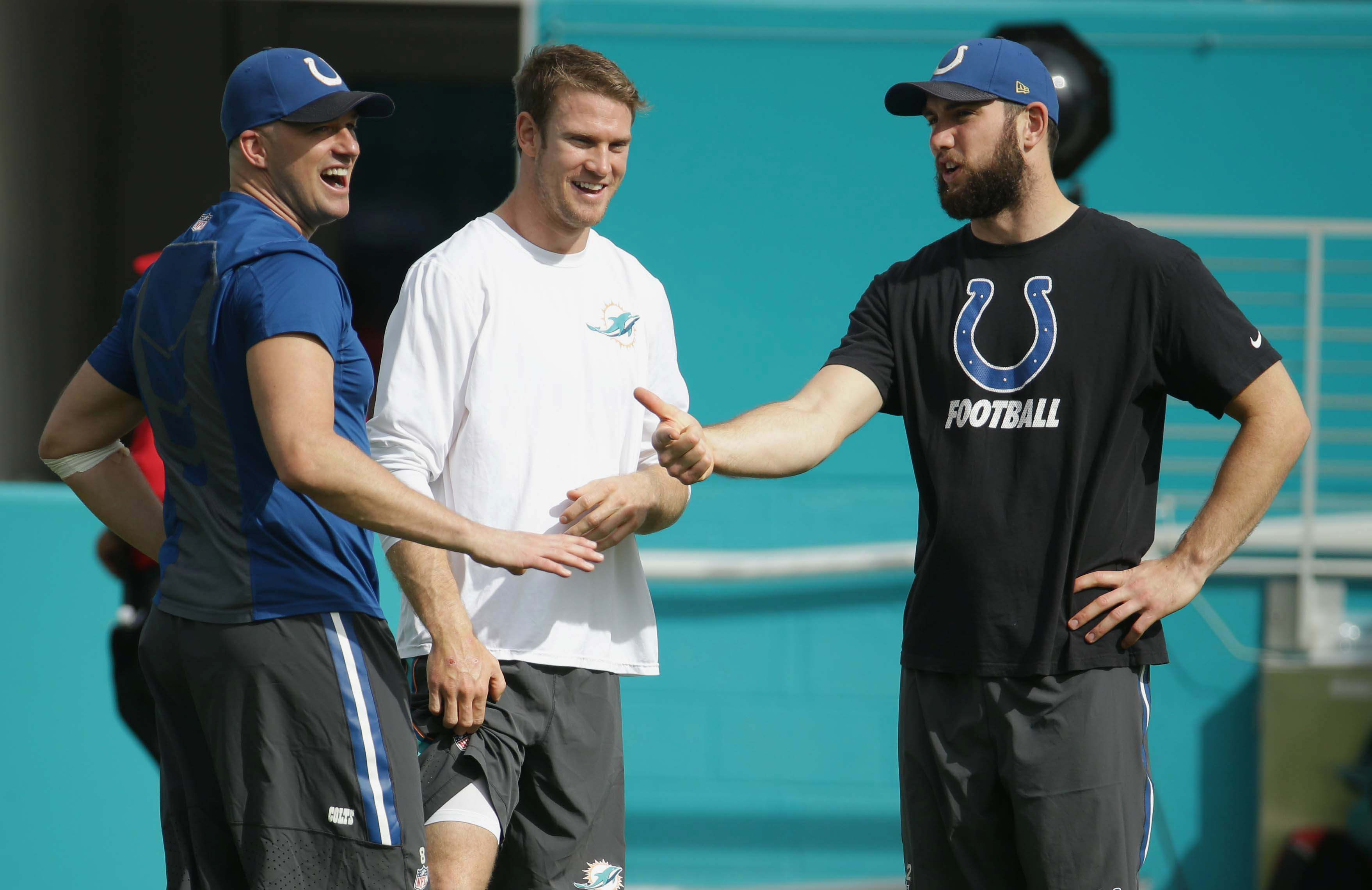 Indianapolis Colts quarterbacks Matt Hasselbeck, left  and Andrew Luck, right, talk to Miami Dolphins quarterback Ryan Tannehill before an NFL football game, Sunday, Dec. 27, 2015, in Miami Gardens, Fla.  (AP Photo/Lynne Sladky)