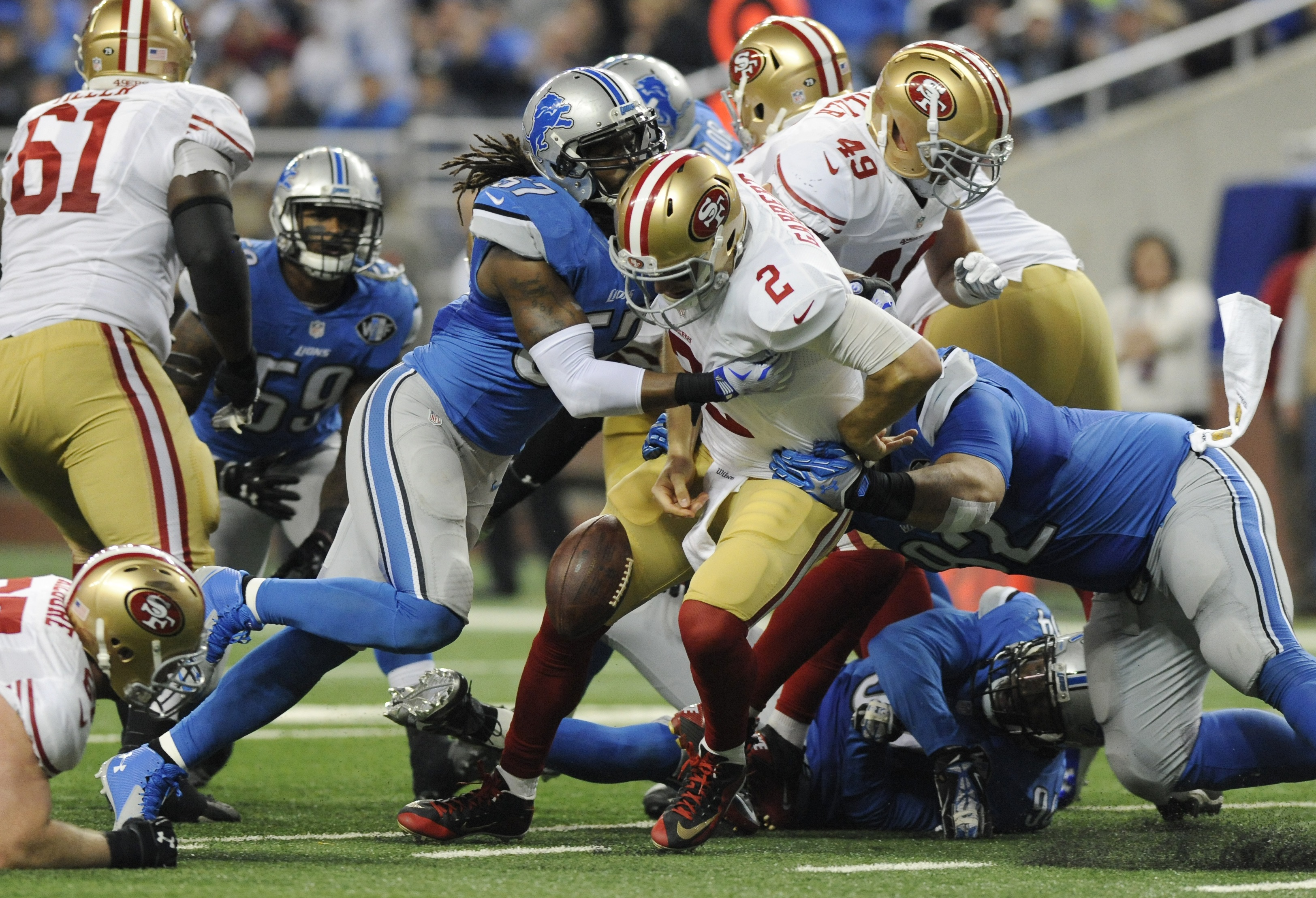 San Francisco 49ers quarterback Blaine Gabbert (2) loses control of the ball and fumbles during a hit by Detroit Lions outside linebacker Josh Bynes (57) during the first half of an NFL football game, Sunday, Dec. 27, 2015, in Detroit. (AP Photo/Jose Juar