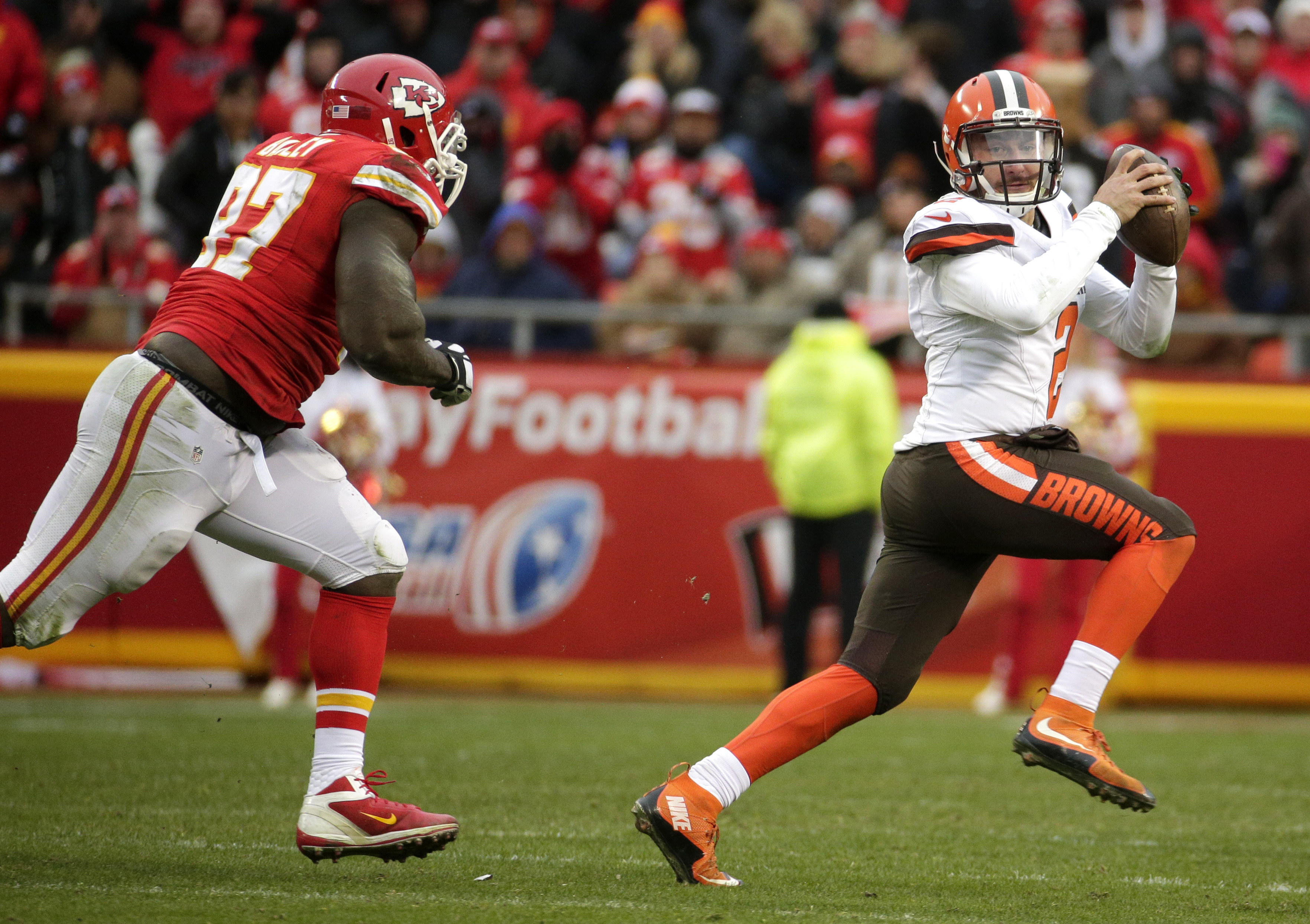 Cleveland Browns quarterback Johnny Manziel, right, runs away from Kansas City Chiefs defensive end Allen Bailey (97) during the second half of an NFL football game in Kansas City, Mo., Sunday, Dec. 27, 2015. (AP Photo/Charlie Riedel)