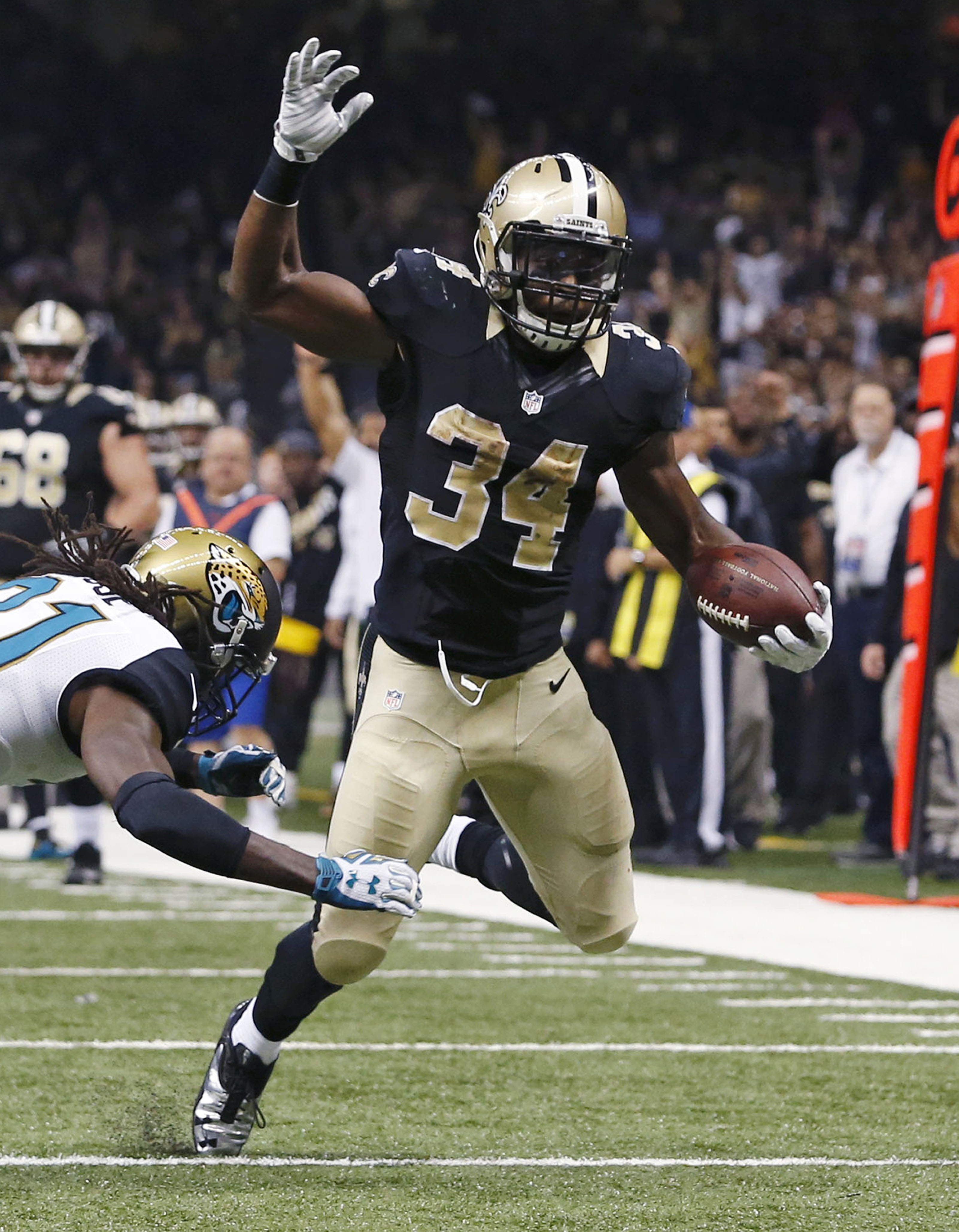 New Orleans Saints running back Tim Hightower (34) carries for a first and goal against Jacksonville Jaguars cornerback Davon House (31) in the first half of an NFL football game in New Orleans, Sunday, Dec. 27, 2015. (AP Photo/Jonathan Bachman)