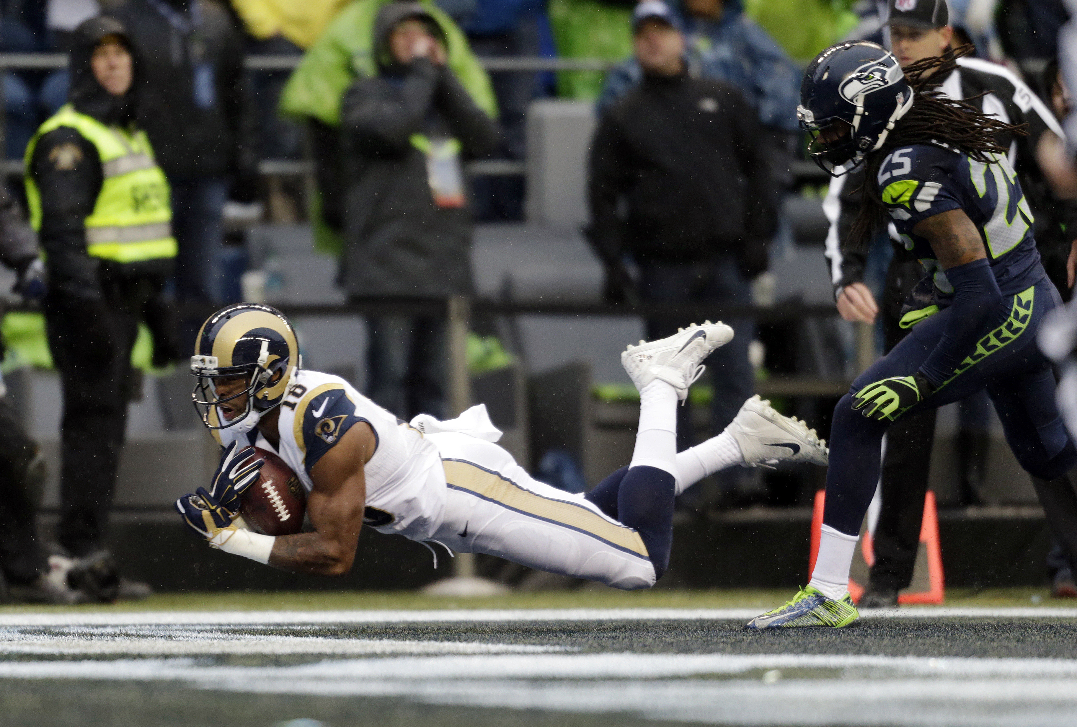 St. Louis Rams' Kenny Britt, left, dives into the end zone on a touchdown reception as Seattle Seahawks' Richard Sherman follows in the first half of an NFL football game, Sunday, Dec. 27, 2015, in Seattle. (AP Photo/John Froschauer)