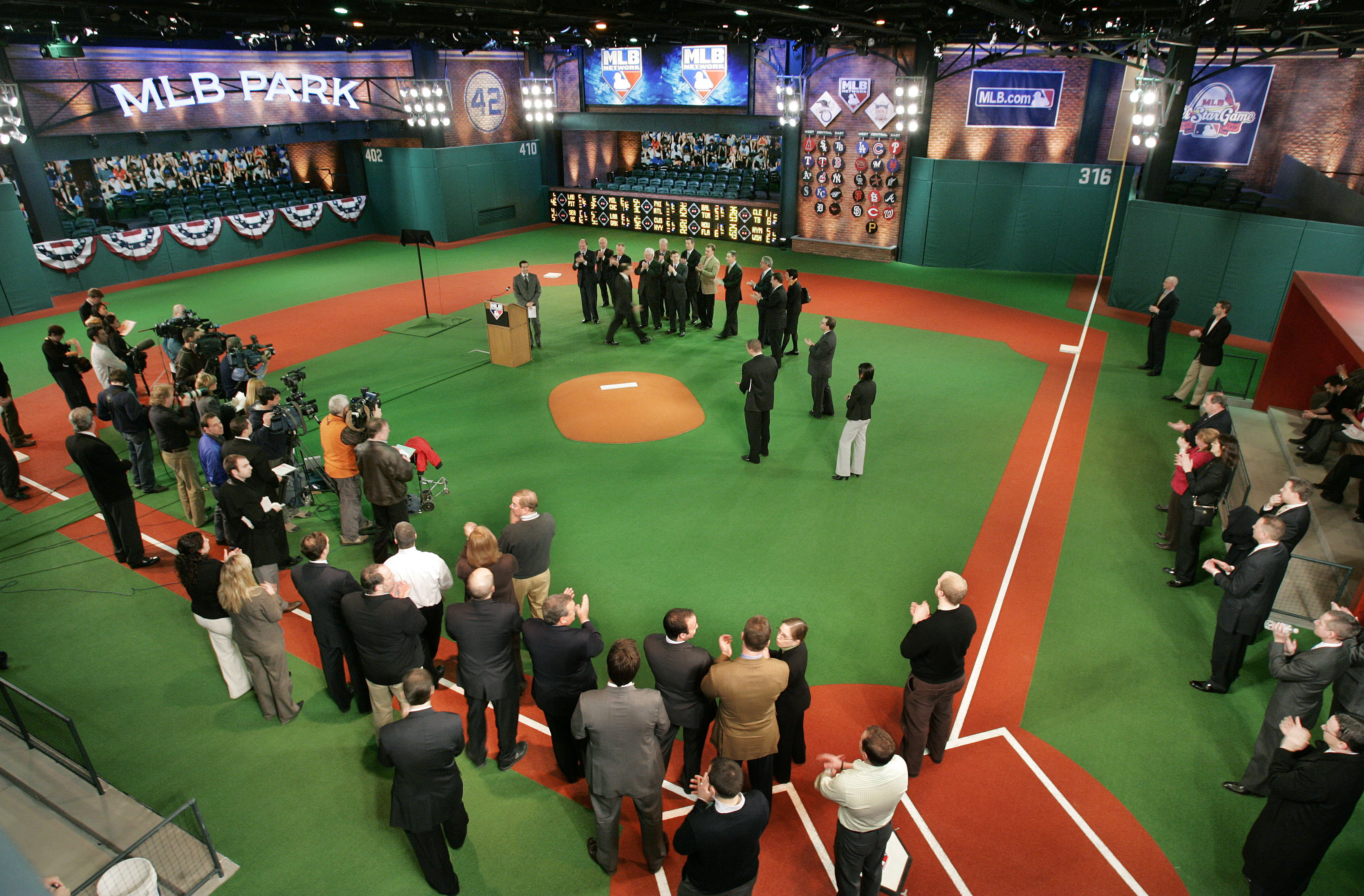 New Jersey Gov. Corzine stands in a group with Major League Baseball officials just beyond a pitchers' mound at the new MLB Network Studios Wednesday, Feb. 4, 2009, in Secaucus, N.J., during the indoor dedication of a street outside the studios of basebal