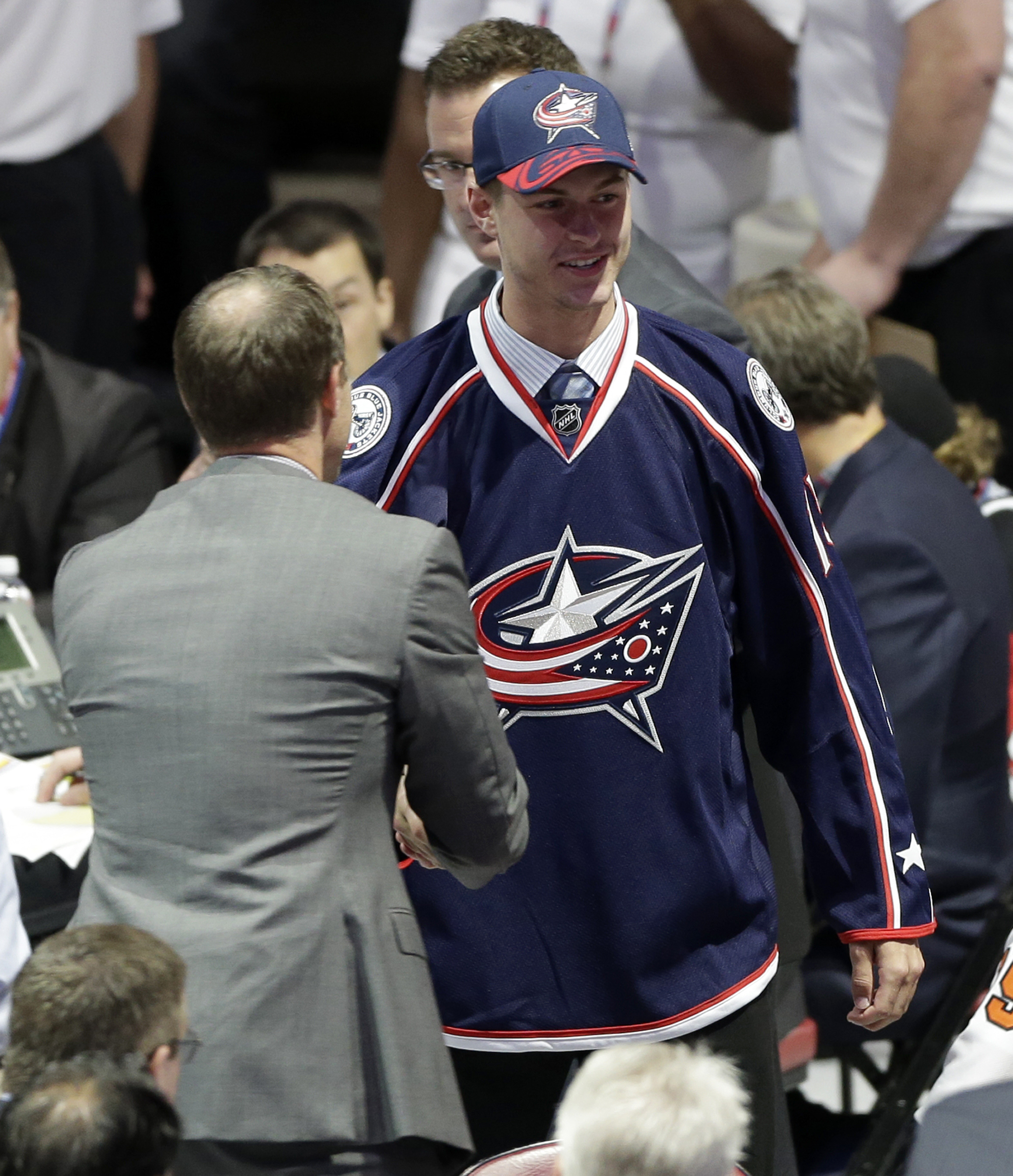 Paul Bittner, right, shakes hands with an executive after being chosen 38th overall by the Columbus Blue Jackets during the second round of the NHL hockey draft, Saturday, June 27, 2015, in Sunrise, Fla. (AP Photo/Alan Diaz)
