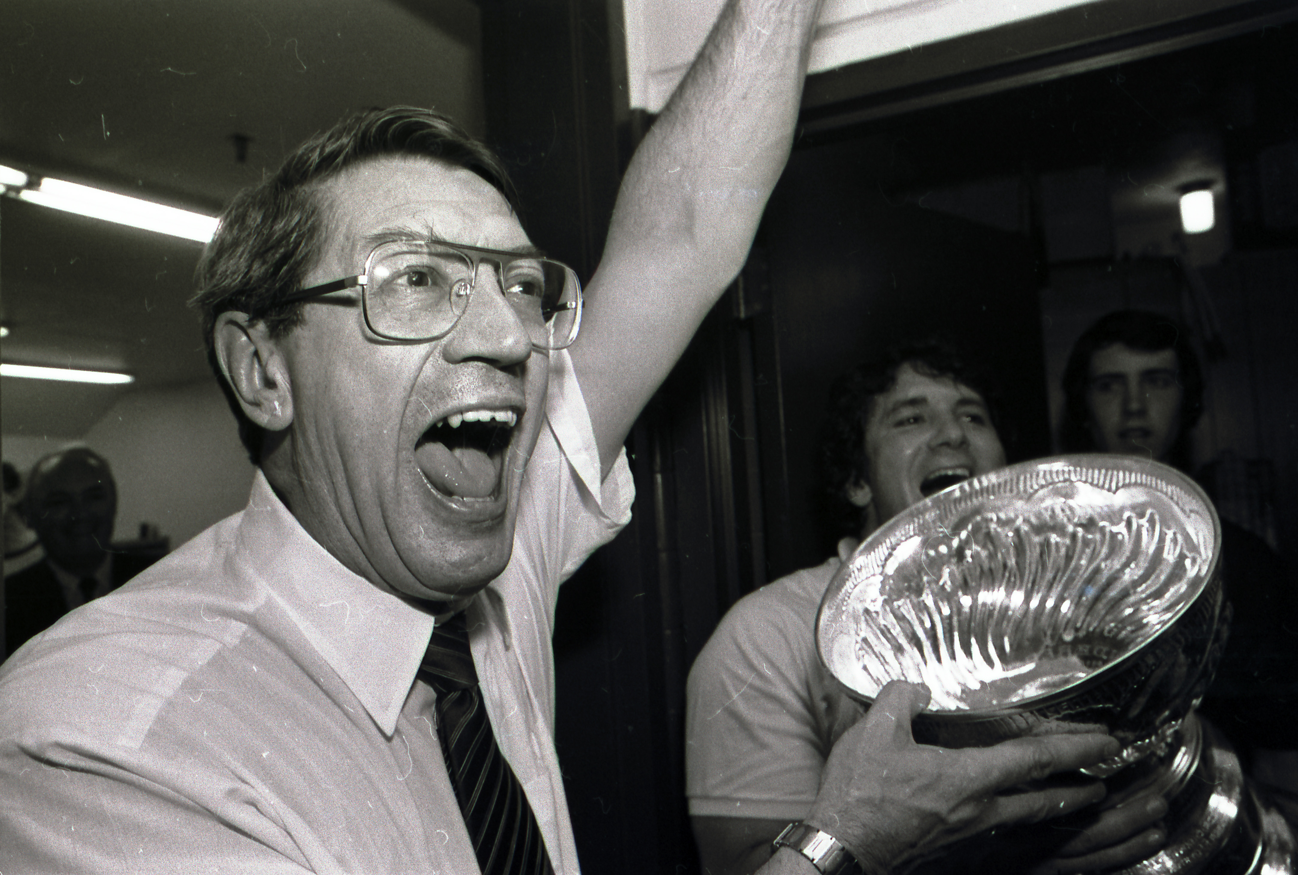 FILE - In this May 17, 1983, file photo, New York Islanders coach Al Arbour celebrates in the locker room as he holds the Stanley Cup after the Islanders won their fourth cup in a row, beating the Edmonton Oilers 4-2 to sweep the series at Nassau Coliseum