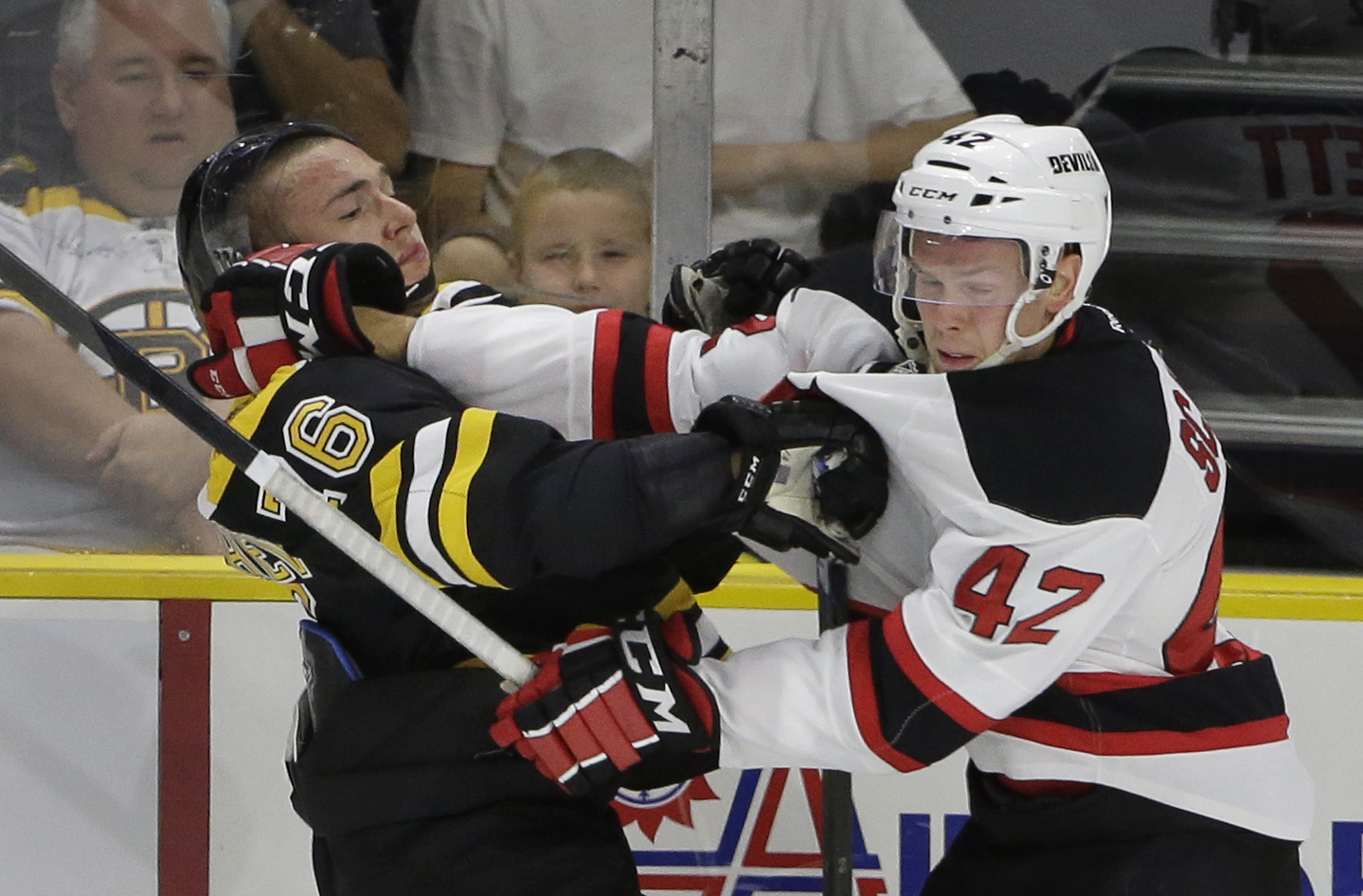 Boston Bruins center Alexander Khokhlachev, of Russia, left, exchanges jabs with New Jersey Devils defenseman Reece Scarlett, right, during the first period of an NHL preseason hockey game, Sunday, Sept. 20, 2015, in Providence, R.I. (AP Photo/Steven Senn
