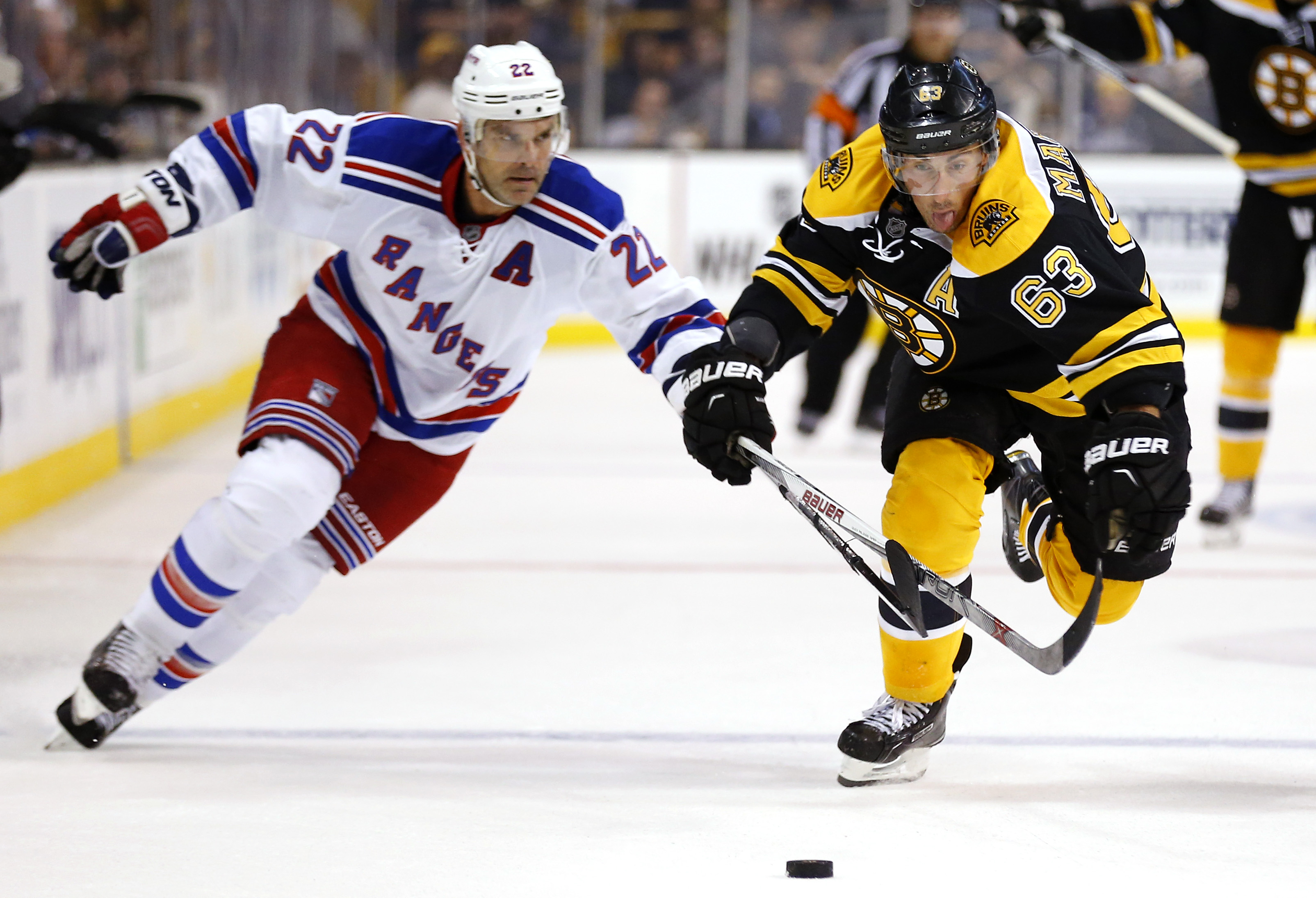Boston Bruins' Brad Marchand (63) chases a loose puck with New York Rangers' Dan Boyle during the second period of an NHL preseason hockey game in Boston on Thursday, Sept. 24, 2015. (AP Photo/Winslow Townson)