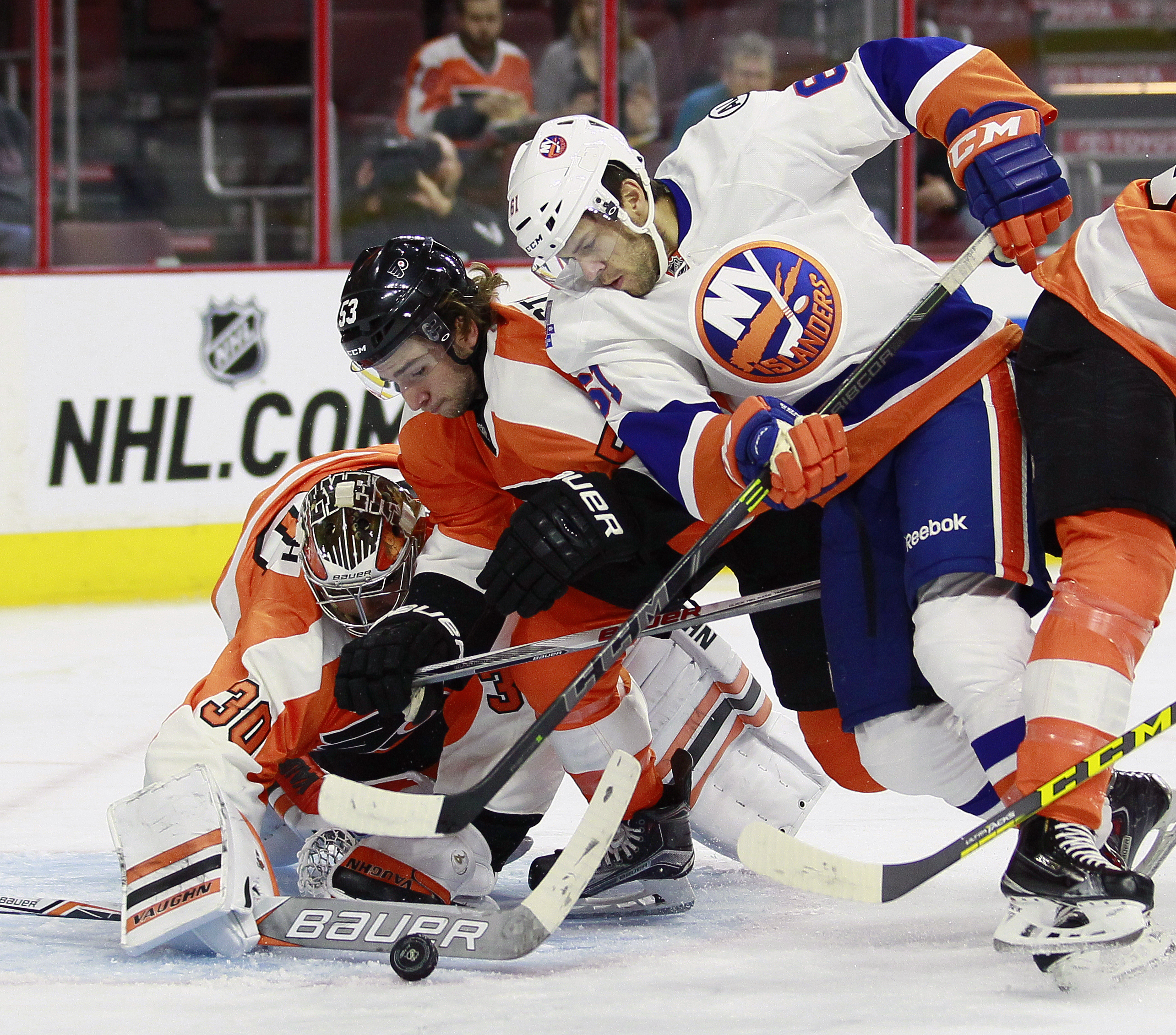 Philadelphia Flyers goalie Michal Neuvirth, left, Flyers' Shayne Gotisbehere, center and New York Islanders' Tyler Barnes dig for the puck during the first period of a preseason NHL hockey game Friday, Sept. 25, 2015, in Philadelphia. (AP Photo/Tom Mihale