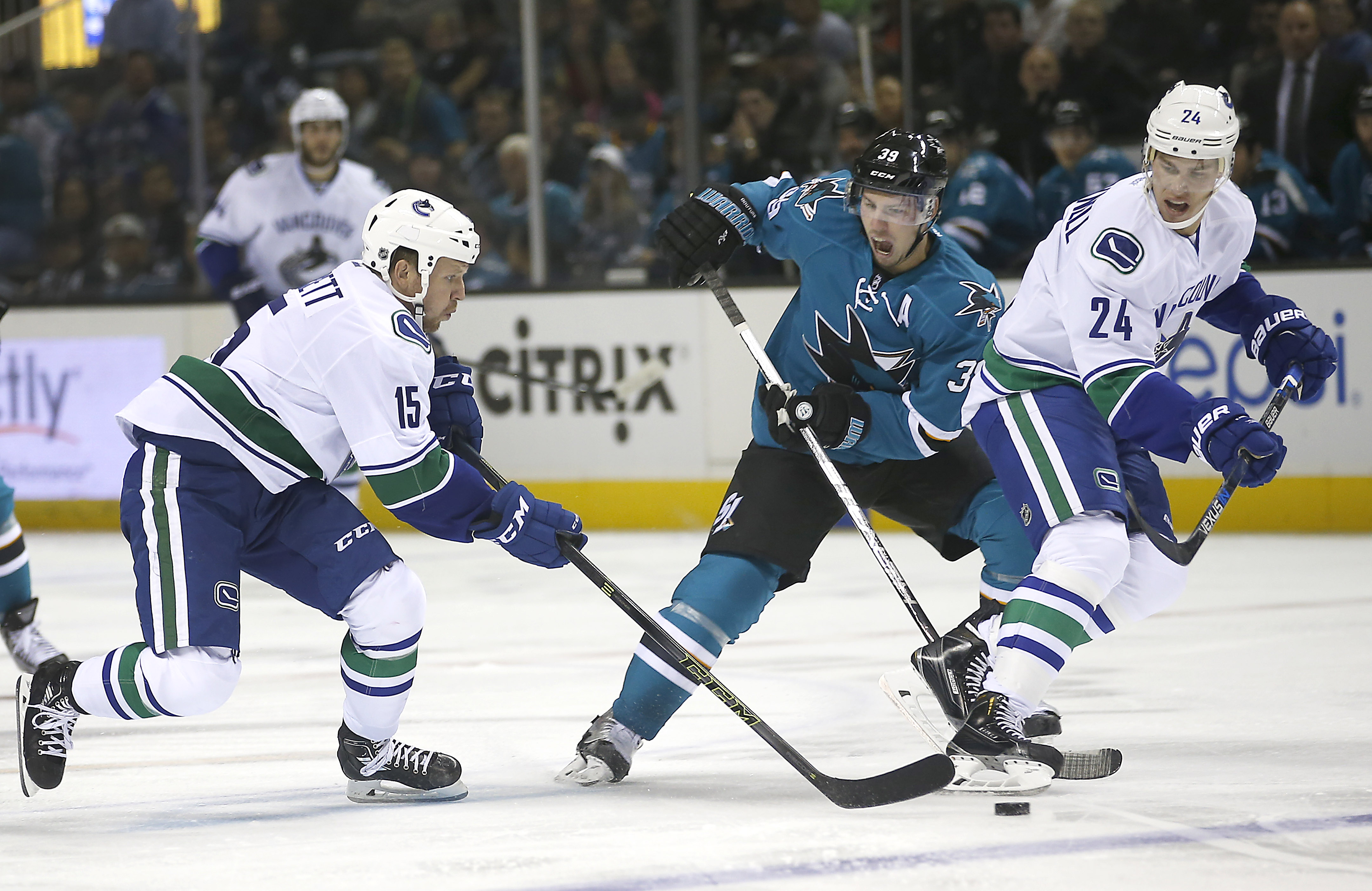 Vancouver Canucks' Derek Dorsett (15) and Adam Cracknell (24) battles for the puck against San Jose Sharks center Logan Couture (39) during the second period of an NHL preseason hockey game Tuesday, Sept. 29, 2015, in San Jose, Calif. (AP Photo/Tony Avela