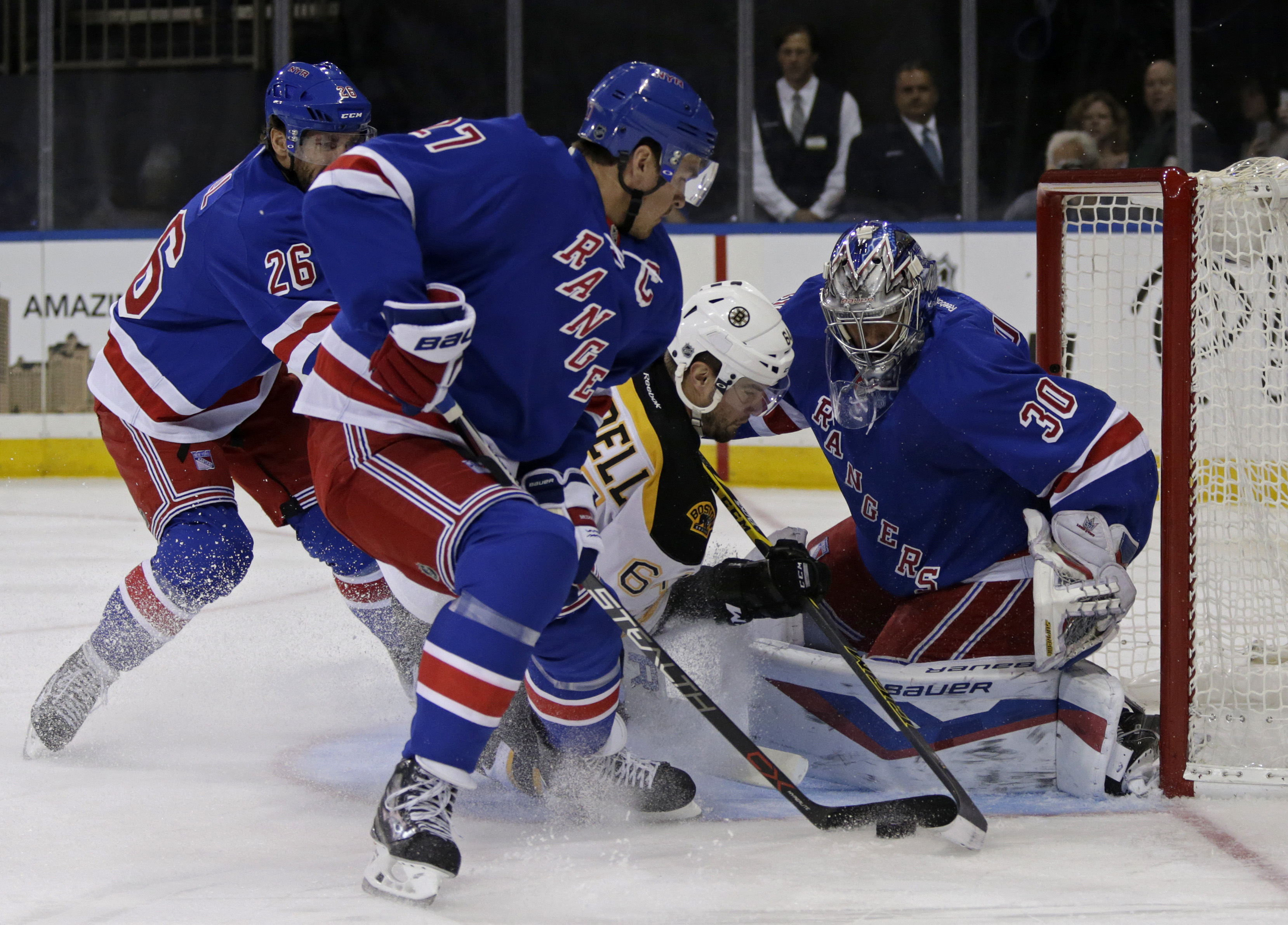 New York Rangers goalie Henrik Lundqvist (30) makes a save on a shot by Boston Bruins right wing Tyler Randell (64) as Rangers defenseman Ryan McDonagh (27) looks on during the first period of an NHL preseason hockey game at Madison Square Garden in New Y