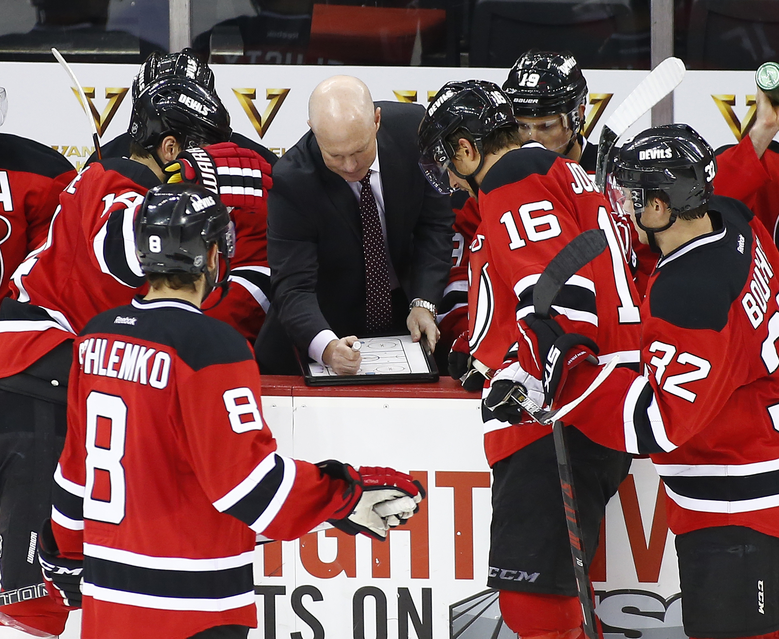 New Jersey Devils head coach John Hynes diagrams a play for his team during a timeout during the third period against the Philadelphia Flyers in an NHL preseason hockey game in Newark, N.J., Friday, Oct 2, 2015. The Devils defeated the Flyers 3-2. (AP Pho