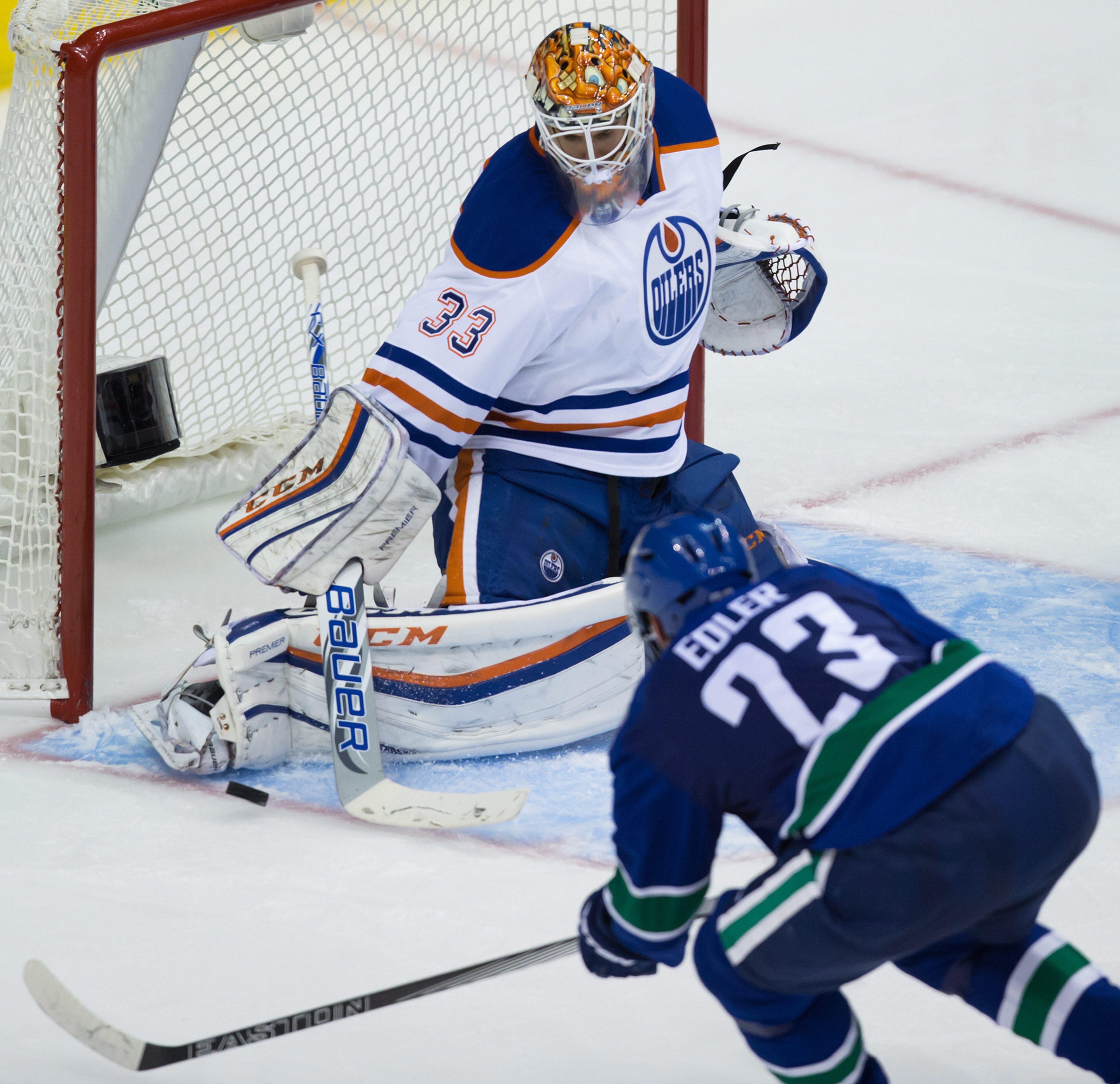 Edmonton Oilers goalie Cam Talbot stops Vancouver Canucks' Alexander Edler, of Sweden, during the third period of a preseason NHL hockey game in Vancouver, British Columbia, Saturday, Oct. 3, 2015. (Darryl Dyck/The Canadian Press via AP) MANDATORY CREDIT
