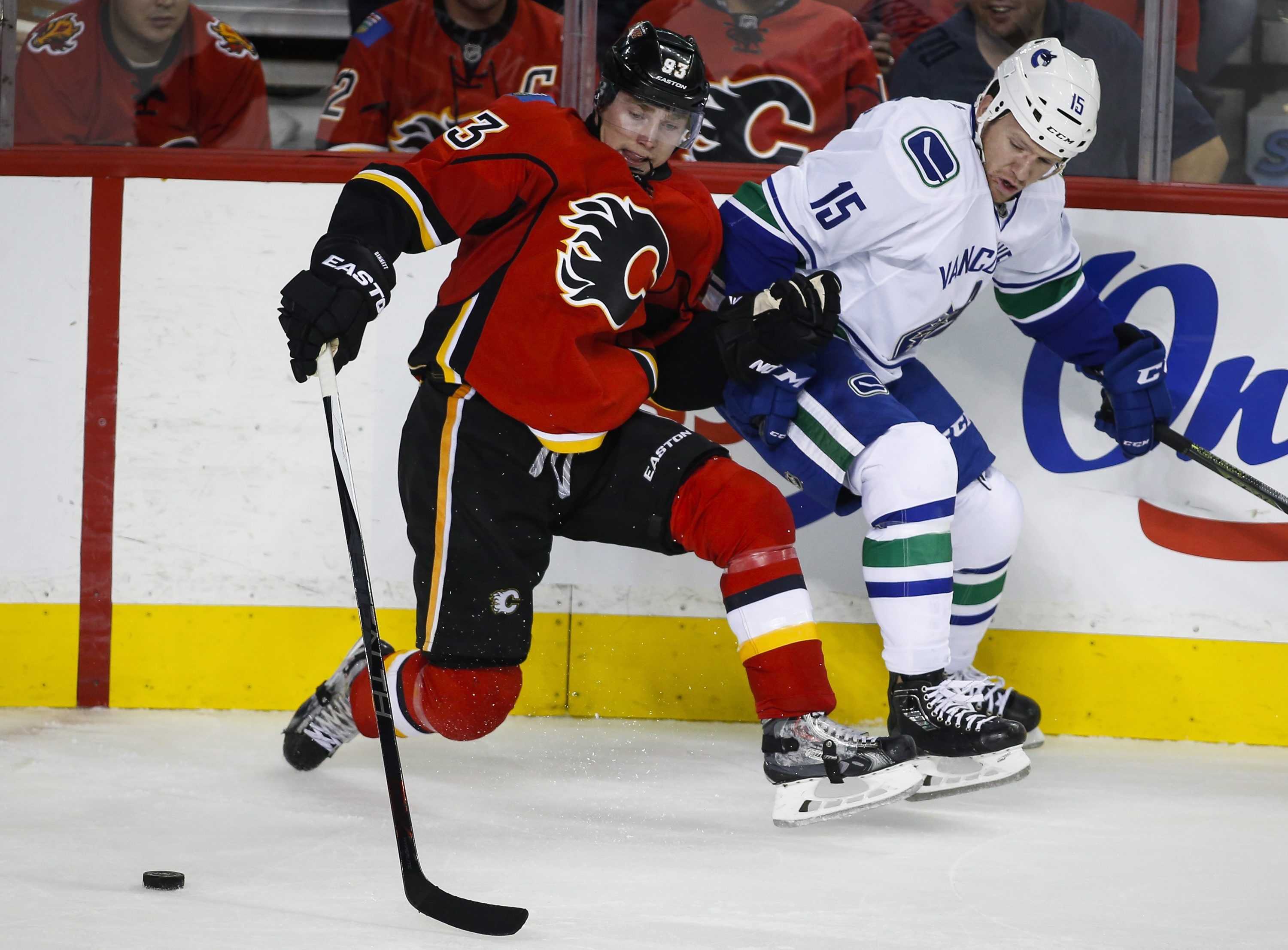 Vancouver Canucks Derek Dorsett, right, and Calgary Flames Sam Bennett battle for the puck during the second period of an NHL hockey game in Calgary, Alberta, Wednesday, Oct. 7, 2015. (Jeff McIntosh/The Canadian Press via AP) MANDATORY CREDIT