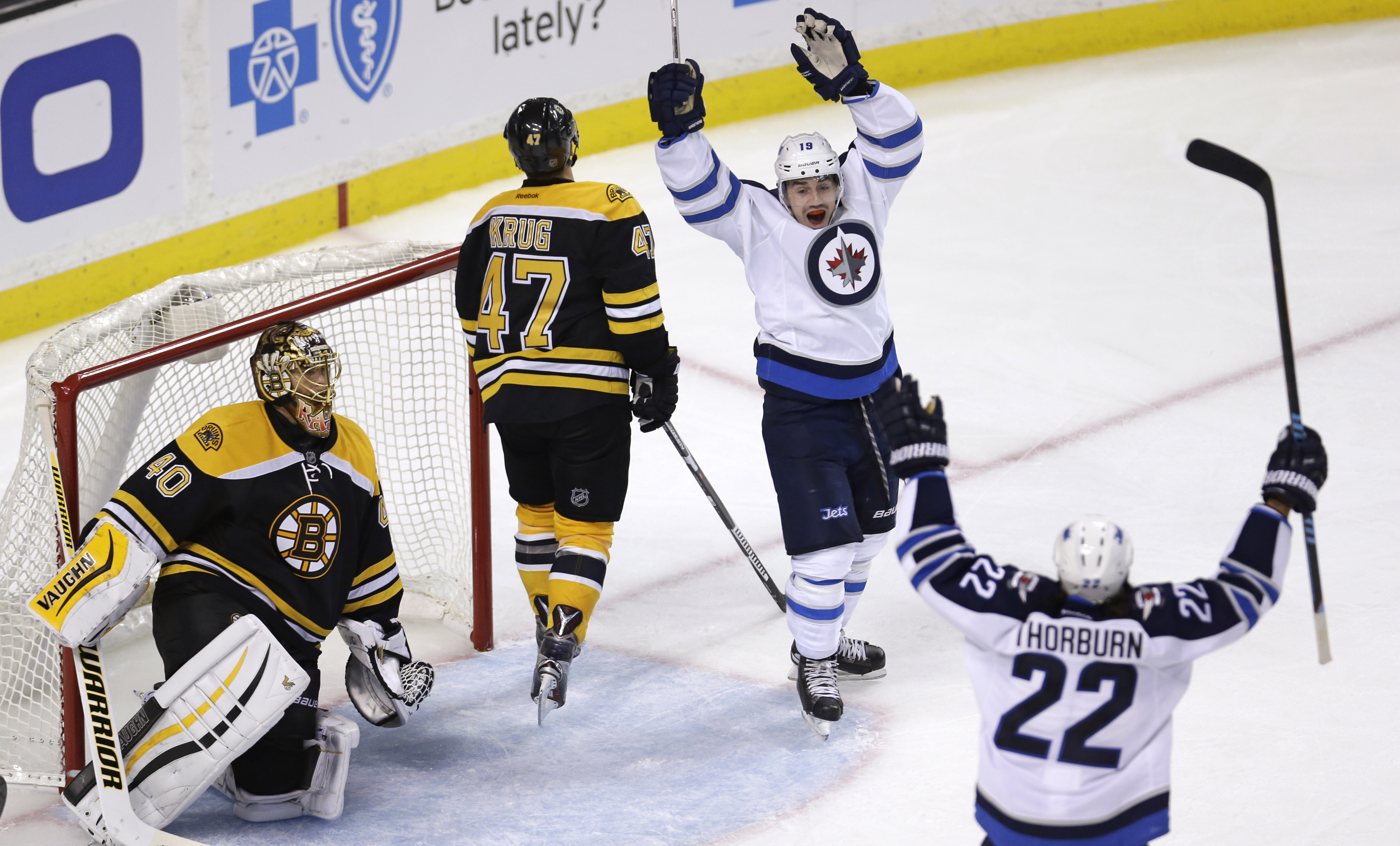 Winnipeg Jets center Nicolas Petan, second from right, celebrates with teammate Chris Thorburn (22) after his goal against Boston Bruins goalie Tuukka Rask, left, of Finland, during the third period of an NHL hockey game in Boston, Thursday, Oct. 8, 2015.