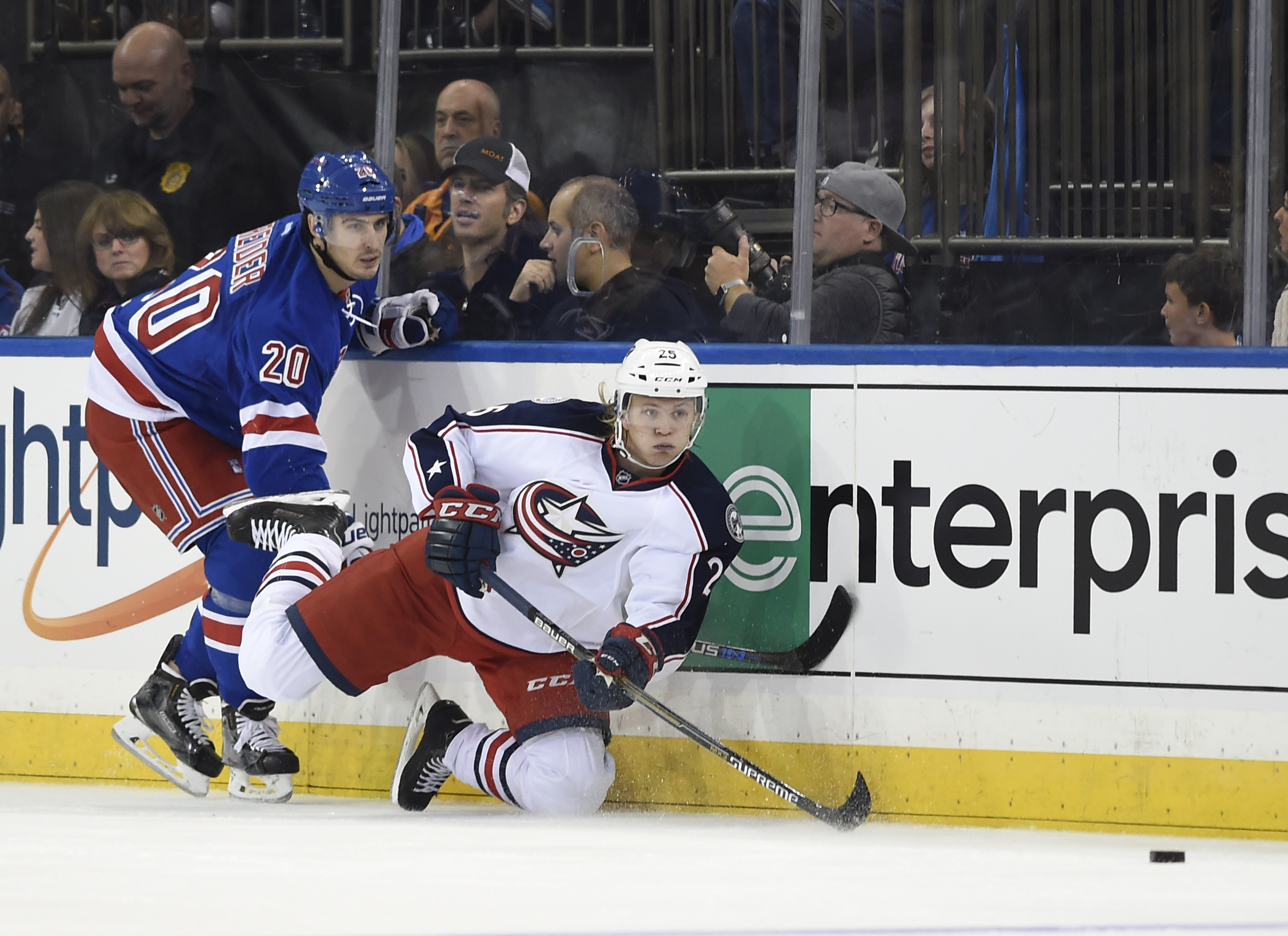 Columbus Blue Jackets center William Karlsson (25) falls to the ice trying to drive the puck away from New York Rangers left wing Chris Kreider (20) during the second period of an NHL hockey game Saturday, Oct. 10, 2015, in New York. (AP Photo/Kathy Kmoni