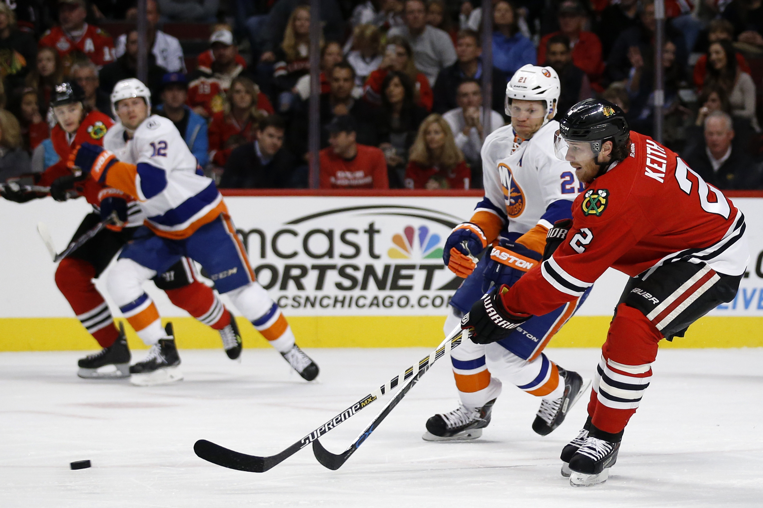 Chicago Blackhawks defenseman Duncan Keith (2) passes past New York Islanders right wing Kyle Okposo (21) during the first period of an NHL hockey game Saturday, Oct. 10, 2015, in Chicago. (AP Photo/Andrew A. Nelles)