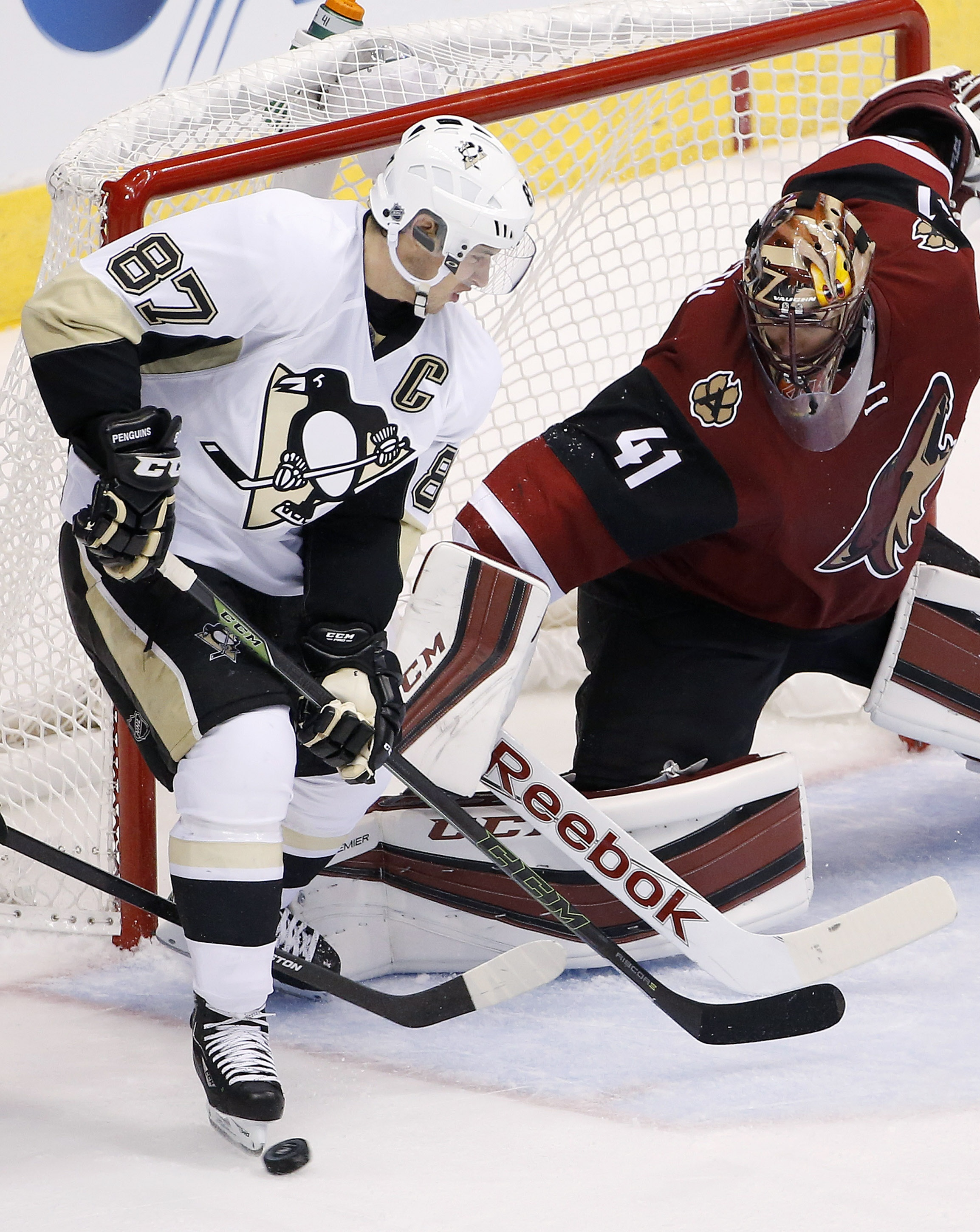 Arizona Coyotes' Mike Smith (41) makes a save in front of Pittsburgh Penguins' Sidney Crosby (87) during the third period of an NHL hockey game Saturday, Oct. 10, 2015, in Glendale, Ariz.  The Coyotes defeated the Penguins 2-1. (AP Photo/Ross D. Franklin)