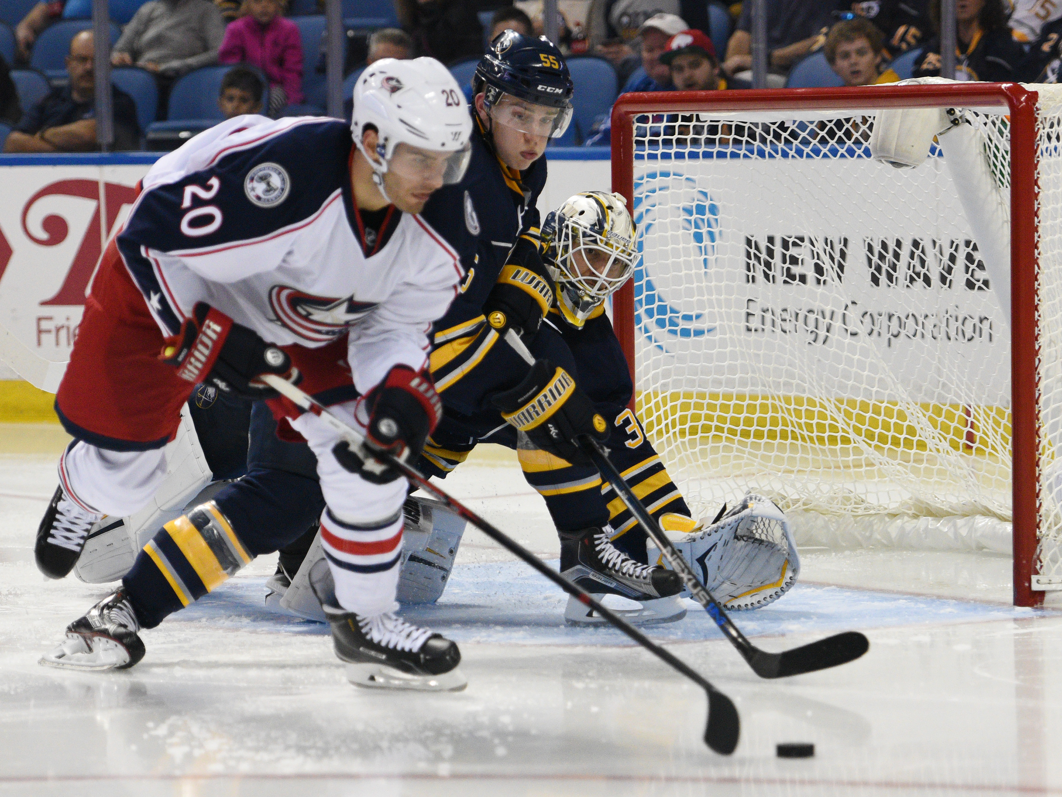 Columbus Blue Jackets left winger Brandon Saad (20) moves the puck in front of Buffalo Sabres defenseman Rasmus Ristolainen (55) and goaltender Chad Johnson (31) during the second period of an NHL hockey game, Monday, Oct. 12, 2015, in Buffalo, N.Y. (AP P
