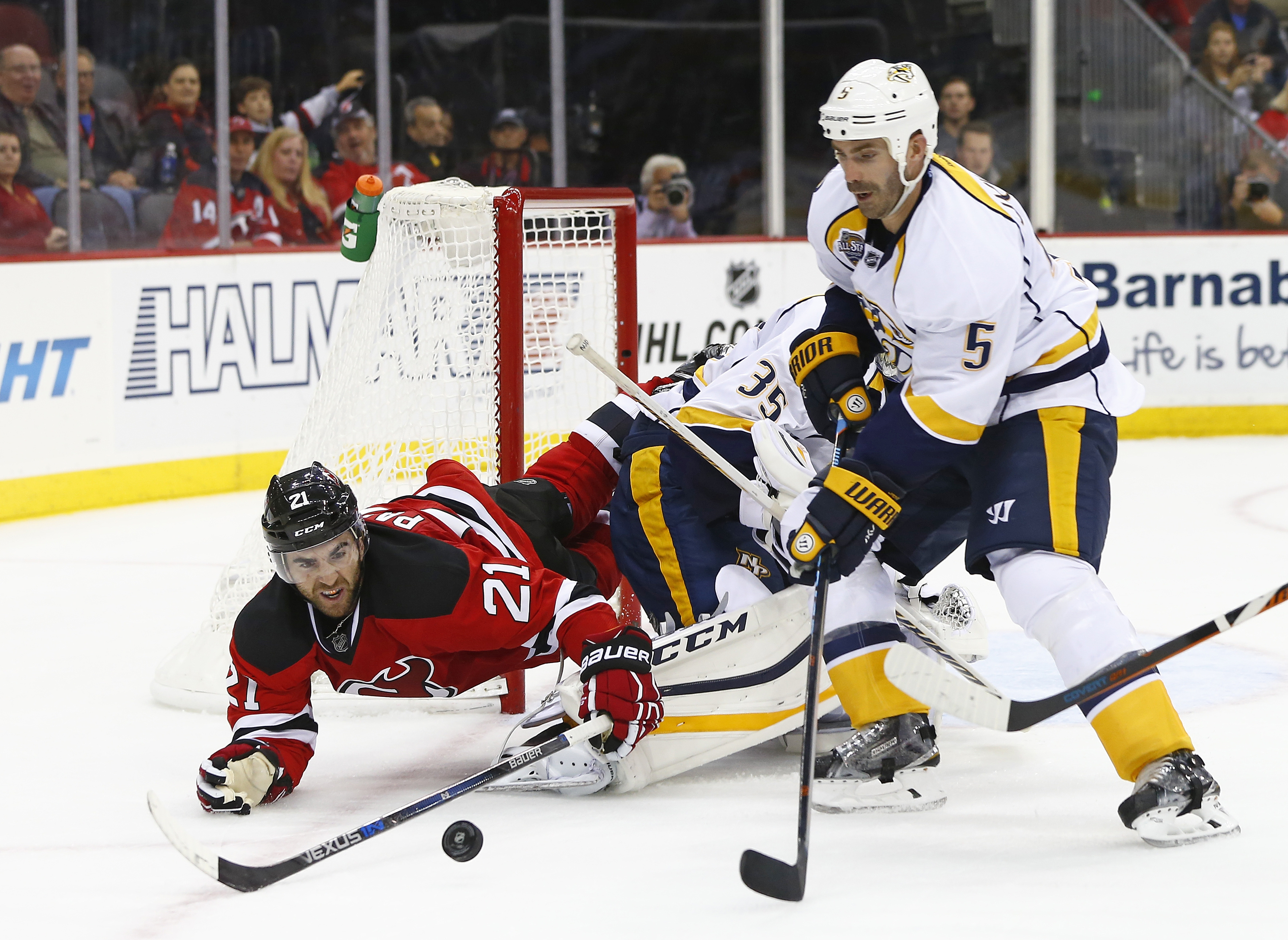 New Jersey Devils Kyle Palmieri (21) trips over Nashville Predators goalie Pekka Rinne (35) of Finland as he battles defensemen Barret Jackman (5) for the puck during the second period of an NHL hockey game in Newark, N.J., Friday, Oct. 13, 2015. (AP Phot