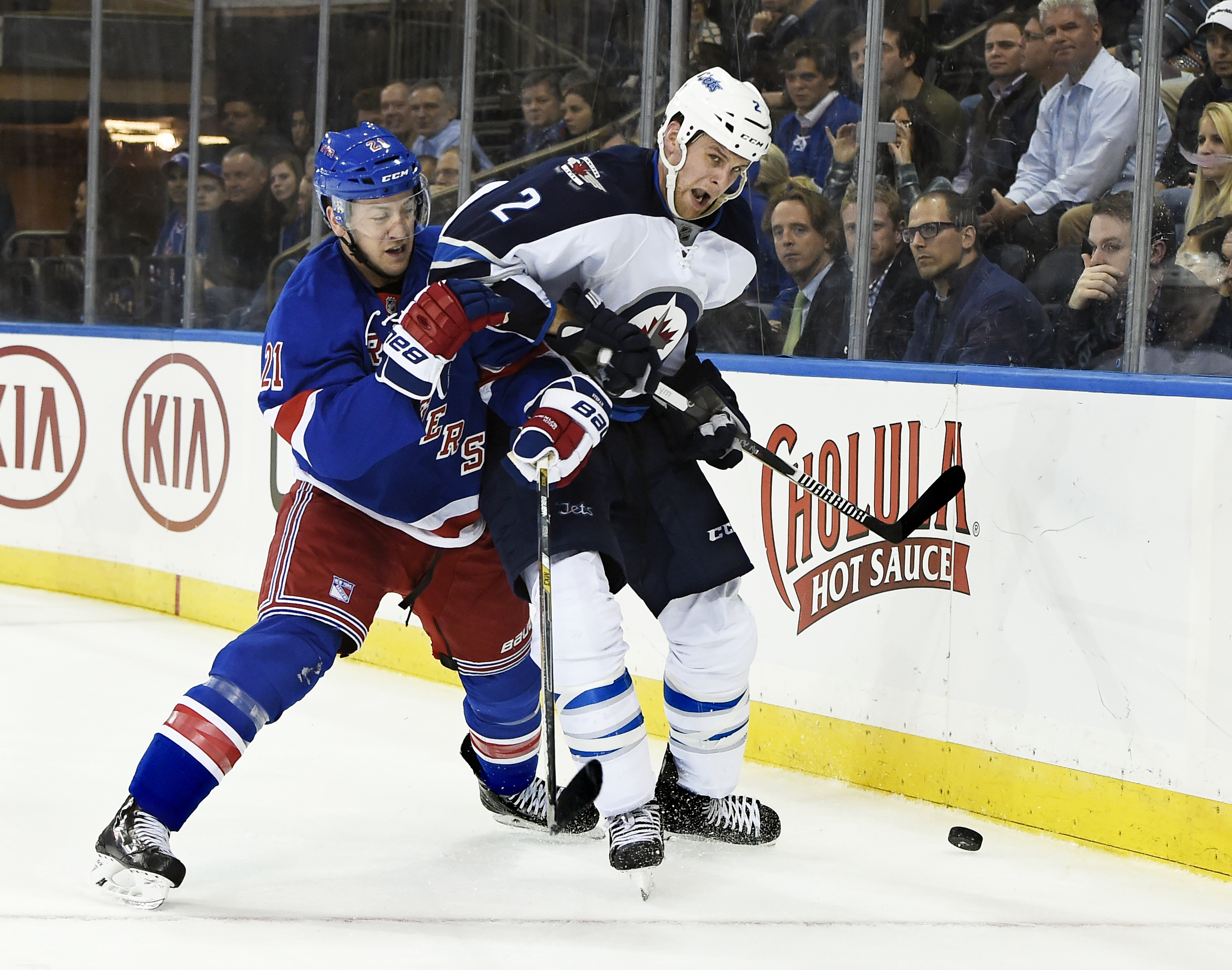 New York Rangers center Derek Stepan (21) shoves Winnipeg Jets defenseman Adam Pardy (2) against the boards during the second period of an NHL hockey game on Tuesday, Oct. 13, 2015, in New York. (AP Photo/Kathy Kmonicek)