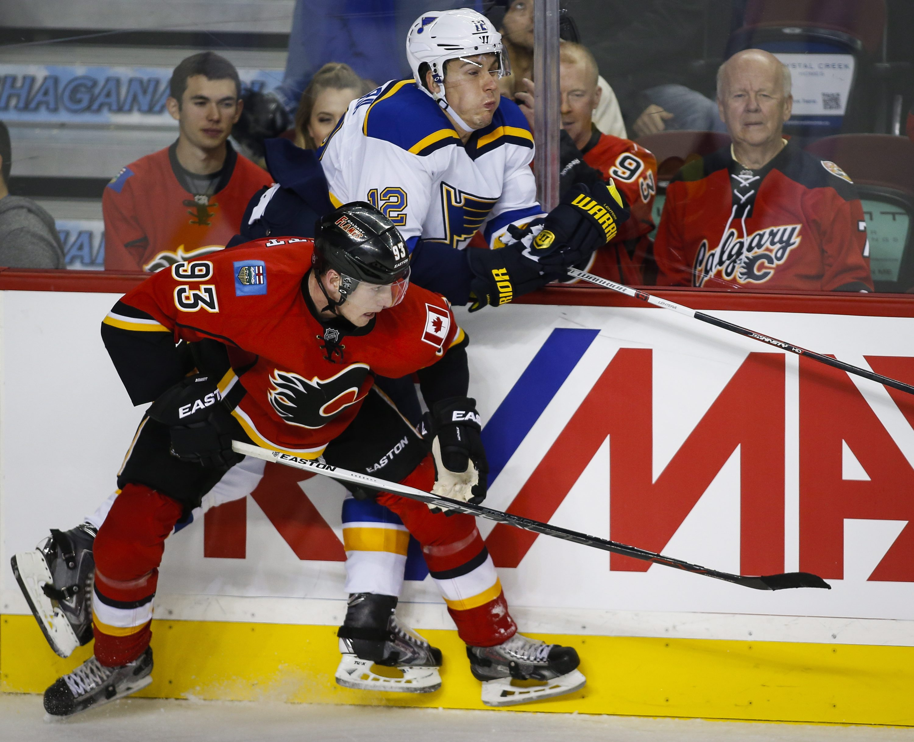 St. Louis Blues' Jori Lehtera, right, from Finland, is checked by Calgary Flames' Sam Bennett during the third period of an NHL hockey game Tuesday, Oct. 13, 2015, in Calgary, Alberta. (Jeff McIntosh/The Canadian Press via AP) MANDATORY CREDIT