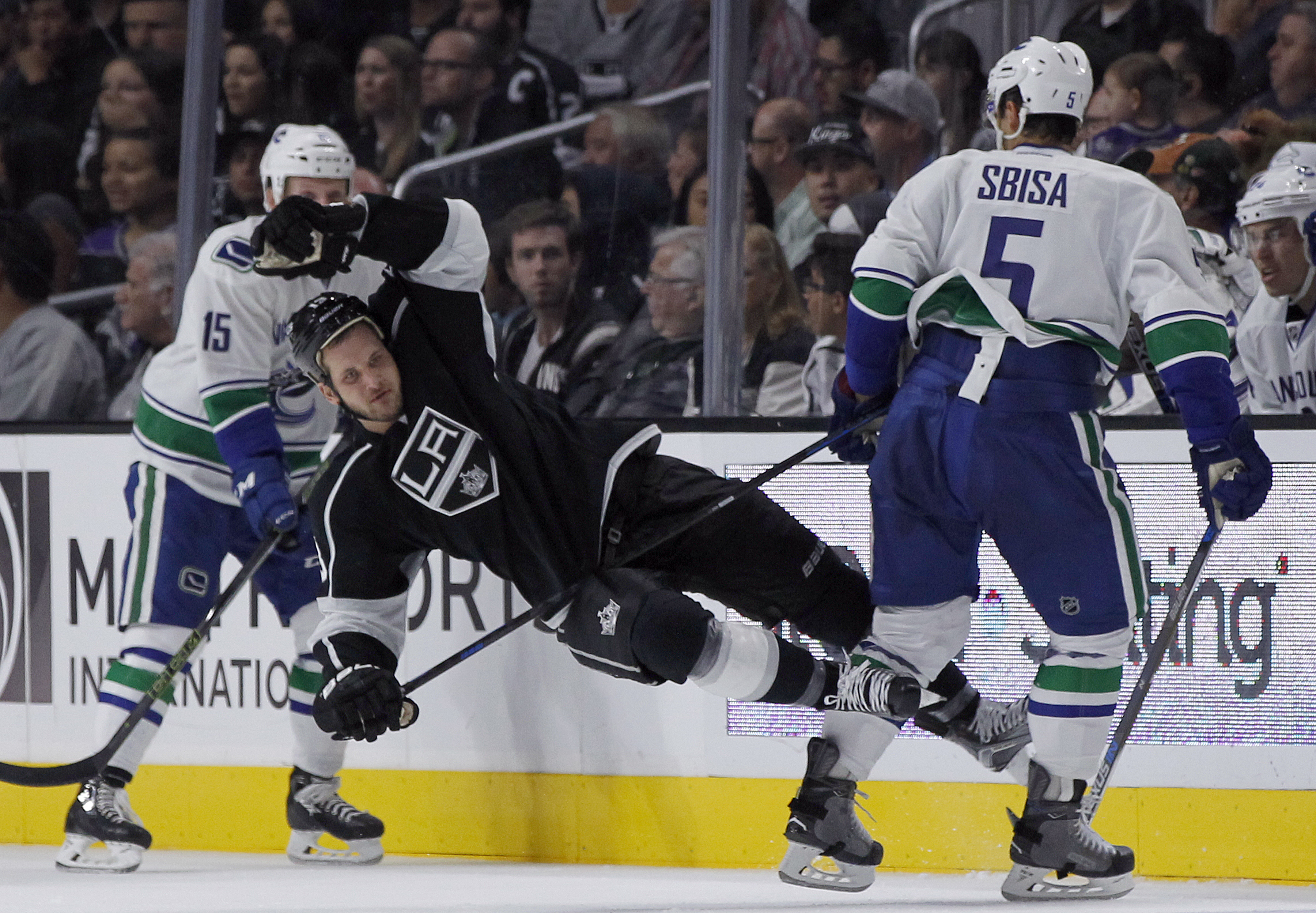 Los Angeles Kings left wing Kyle Clifford, center, gets knocked to the ice by Vancouver Canucks defenseman Luca Sbisa (5), of Italy, during the second period of an NHL hockey game in Los Angeles, Tuesday, Oct. 13, 2015. (AP Photo/Alex Gallardo)