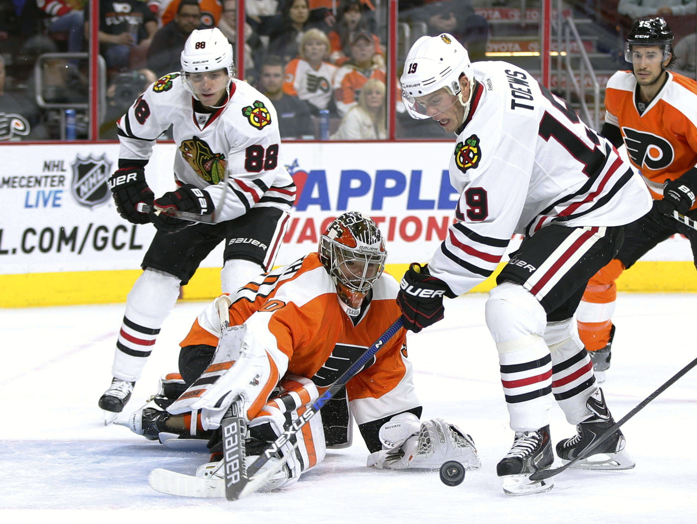 Philadelphia Flyers goalie Michal Neuvirth, center, of Czech Republic knocks the puck away from Chicago Blackhawks center Jonathan Toews, right, with right wing Patrick Kane, left, behind them during the third period of a hockey game, Wednesday, Oct. 14,