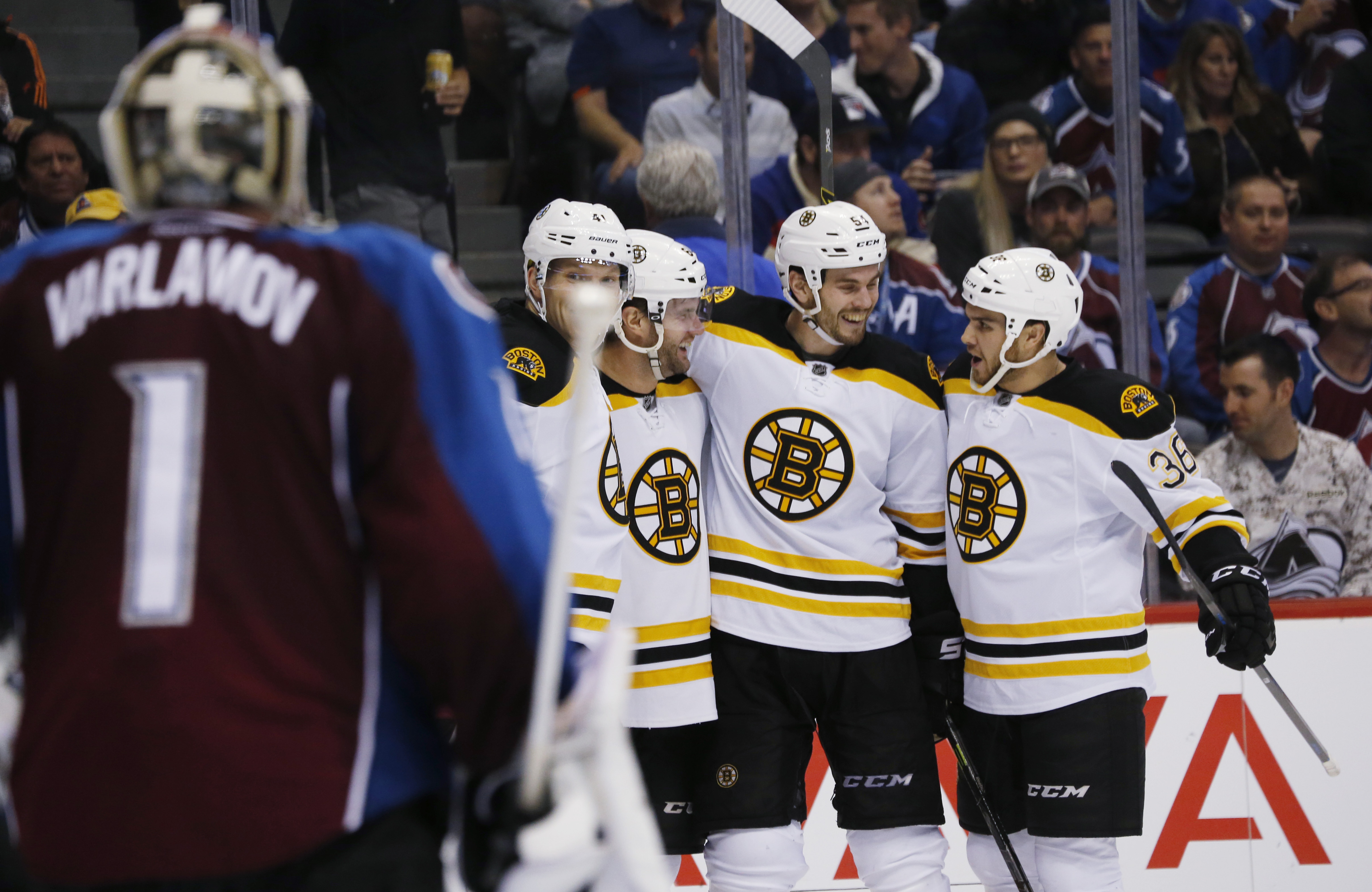 Colorado Avalanche goalie Semyon Varlamov, front, of Russia, watches as Boston Bruins left wing Joonas Kemppainen, back left, of Finland, celebrates with right wing Tyler Randell, defenseman Adam McQuaid and center Zac Rinaldo, from left at rear, after Ra