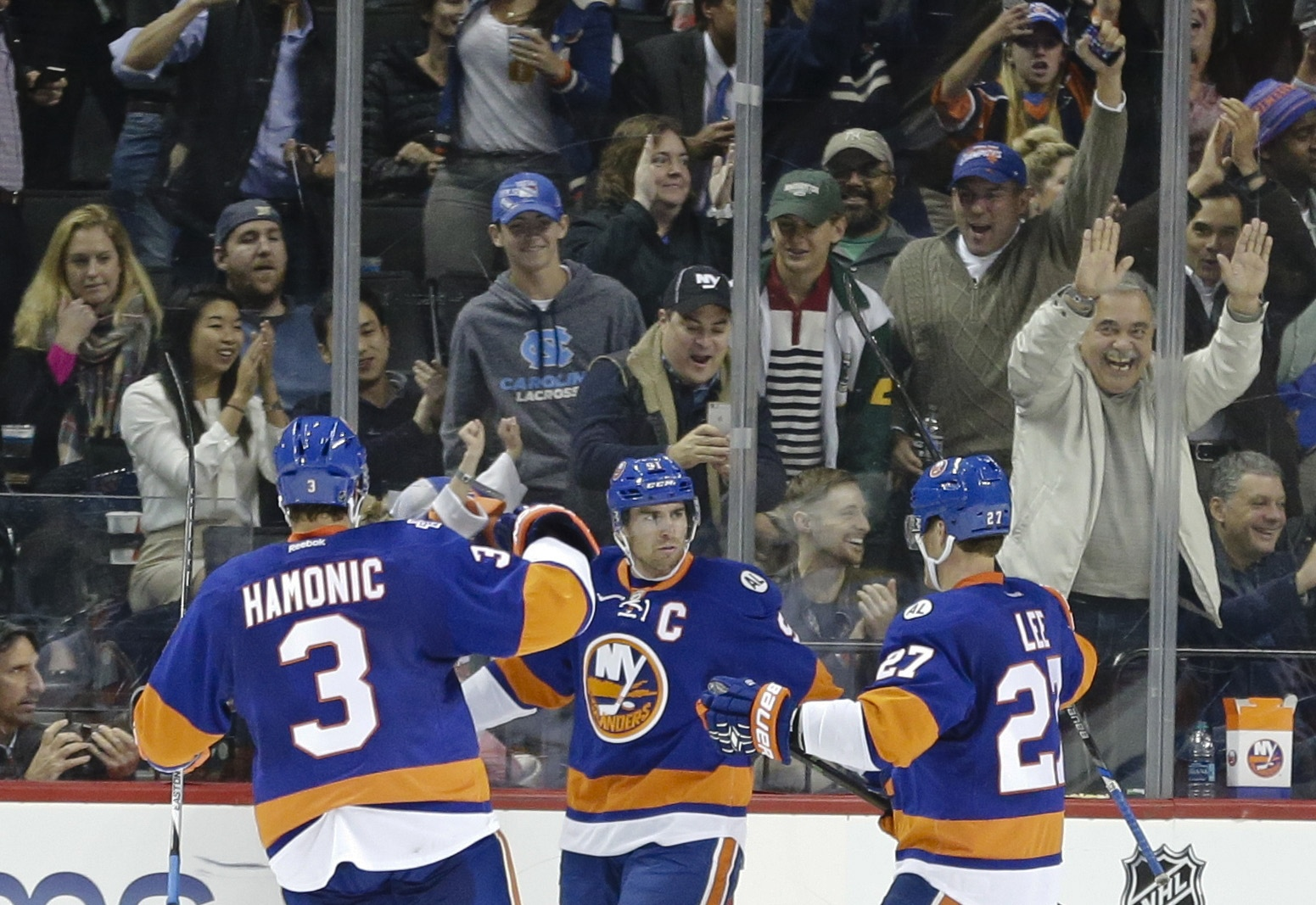 New York Islanders' John Tavares (91) celebrates with teammates Travis Hamonic (3) and Anders Lee (27) after scoring a goal during the third period of an NHL hockey game against the Nashville Predators Thursday, Oct. 15, 2015, in New York. The Islanders w