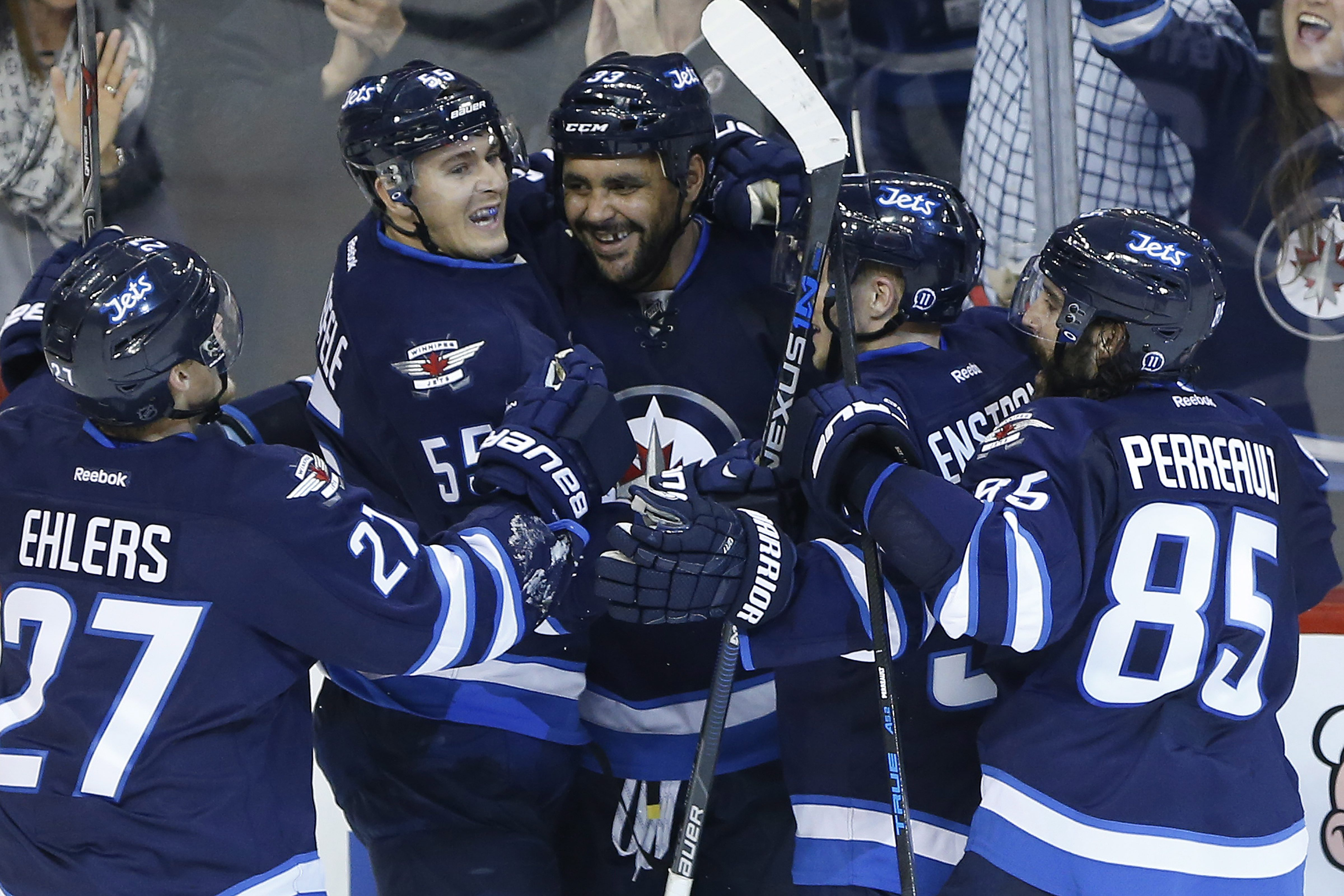 Winnipeg Jets' Nikolaj Ehlers (27), left to right, Mark Scheifele (55), Dustin Byfuglien (33), Toby Enstrom (39) and Mathieu Perreault (85) celebrate Byfuglien's goal against the Calgary Flames during the third period of an NHL hockey game, Friday Oct. 16