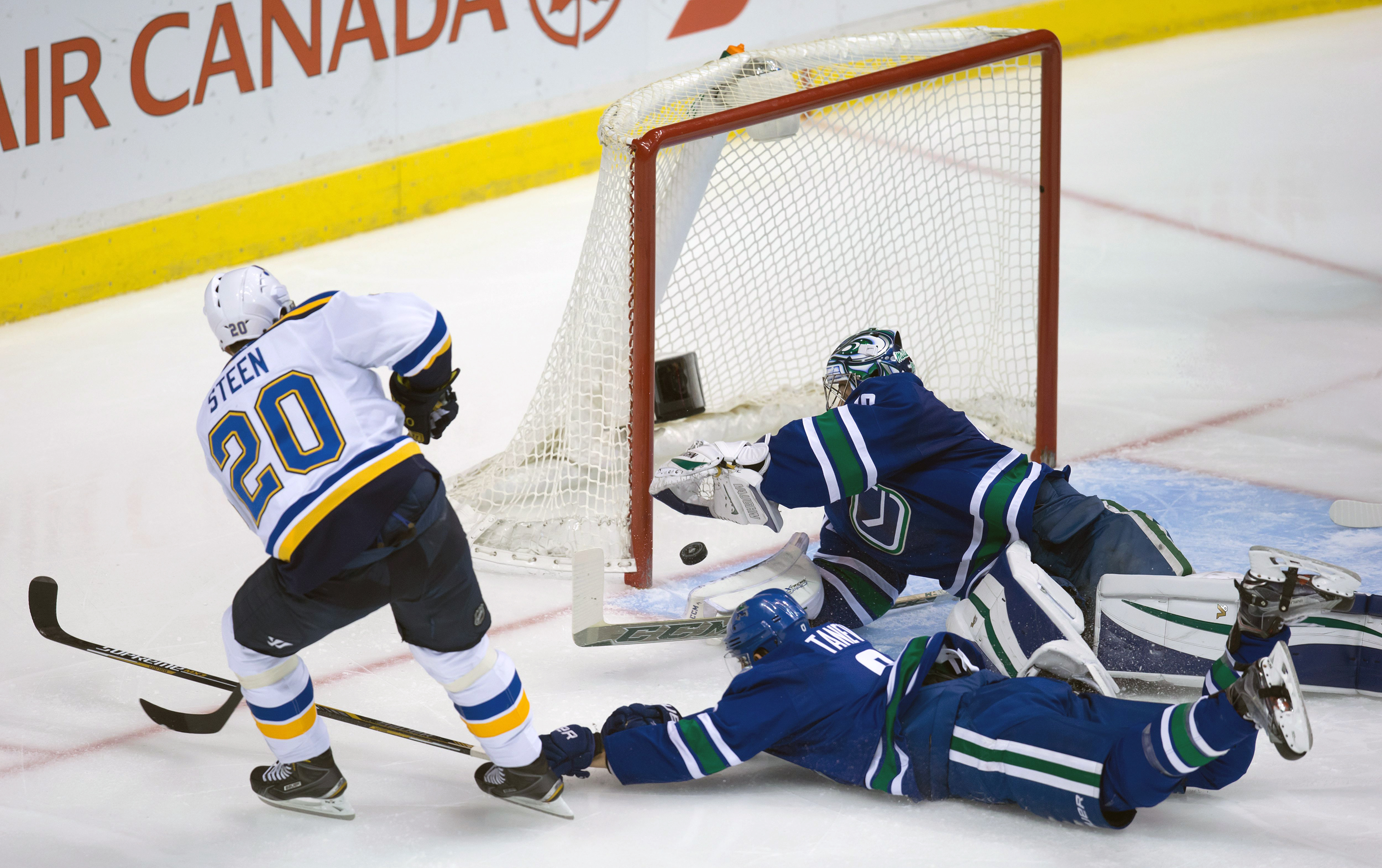 St. Louis Blues' Alexander Steen, left, (20) scores past Vancouver Canucks' goalie Ryan Miller, top right, and a diving Chris Tanev during the second period of an NHL hockey game in Vancouver, British Columbia, Friday, Oct. 16, 2015. (Darryl Dyck/The Cana
