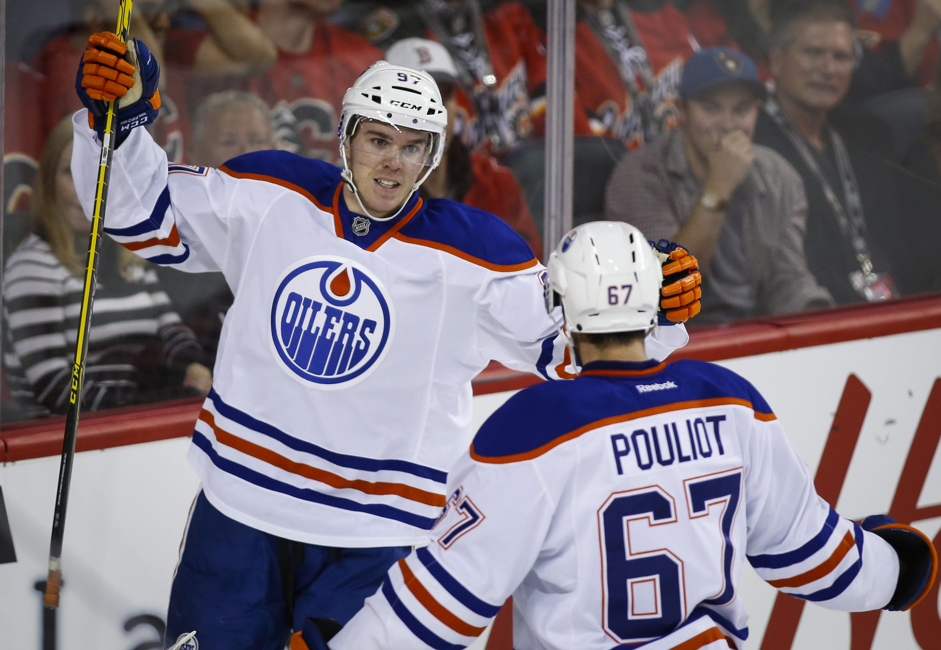 Edmonton Oliers' Connor McDavid, left, celebrates his goal with teammate Benoit Pouliot (67) during the second period of an NHL hockey game against the Calgary Flames on Saturday, Oct. 17, 2015, in Calgary, Alberta. (Jeff McIntosh/The Canadian Press via A