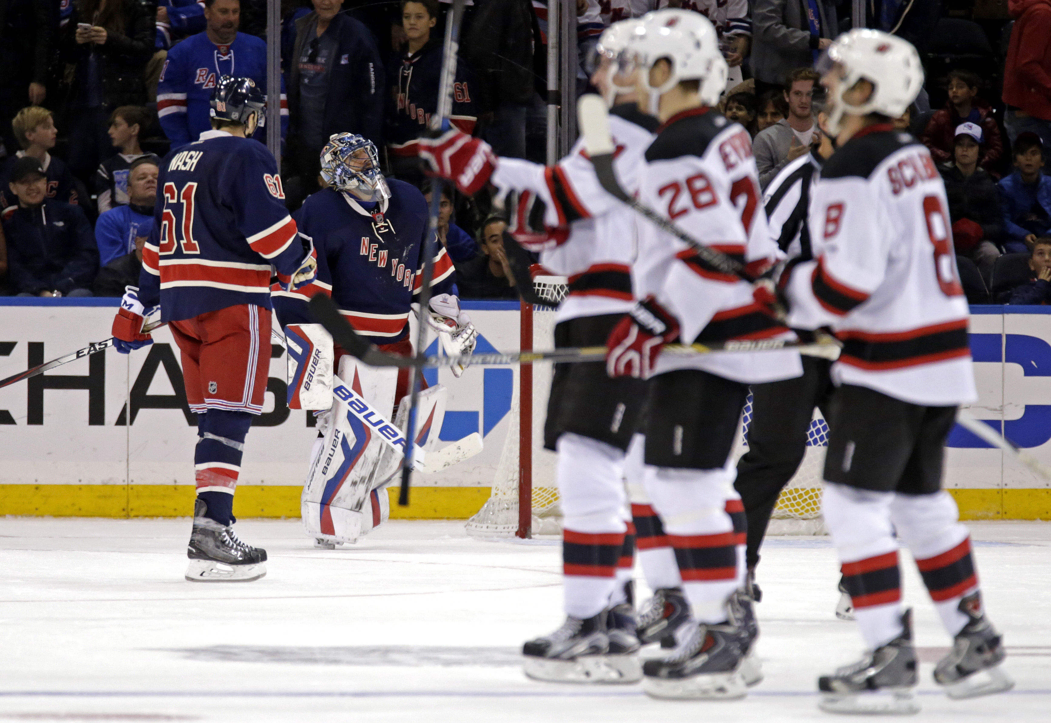 New York Rangers goalie Henrik Lundqvist, second from left, of Sweden, reacts as the New Jersey Devils celebrate after scoring a goal in overtime of an NHL hockey game at Madison Square Garden on Sunday, Oct. 18, 2015, in New York. The Devils defeated the