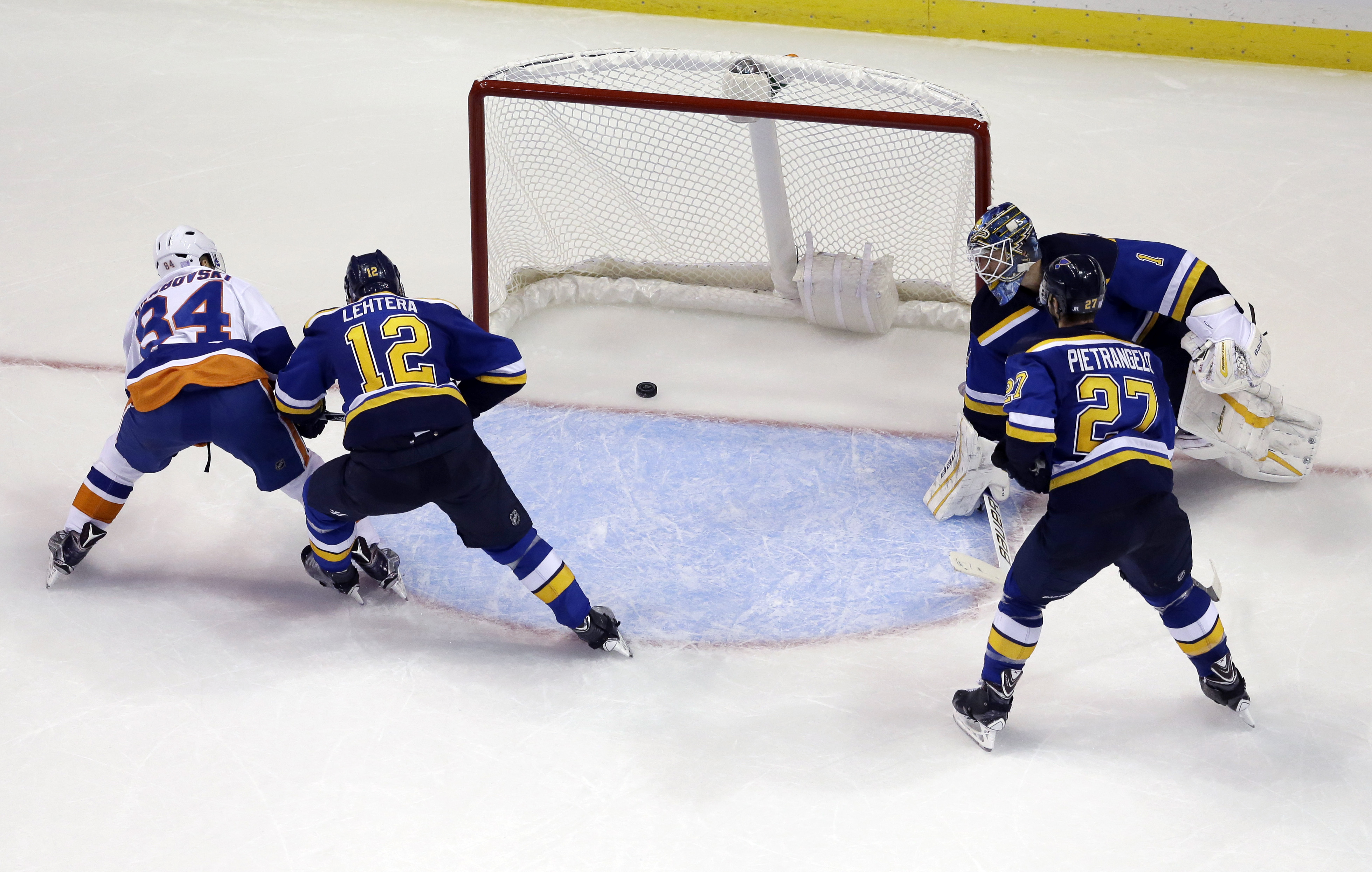 New York Islanders' Mikhail Grabovski, of Germany, scores the game-winning goal past St. Louis Blues goalie Brian Elliott (1), Alex Pietrangelo (27) and Jori Lehtera (12), of Finland, during overtime of an NHL hockey game Saturday, Oct. 24, 2015, in St. L