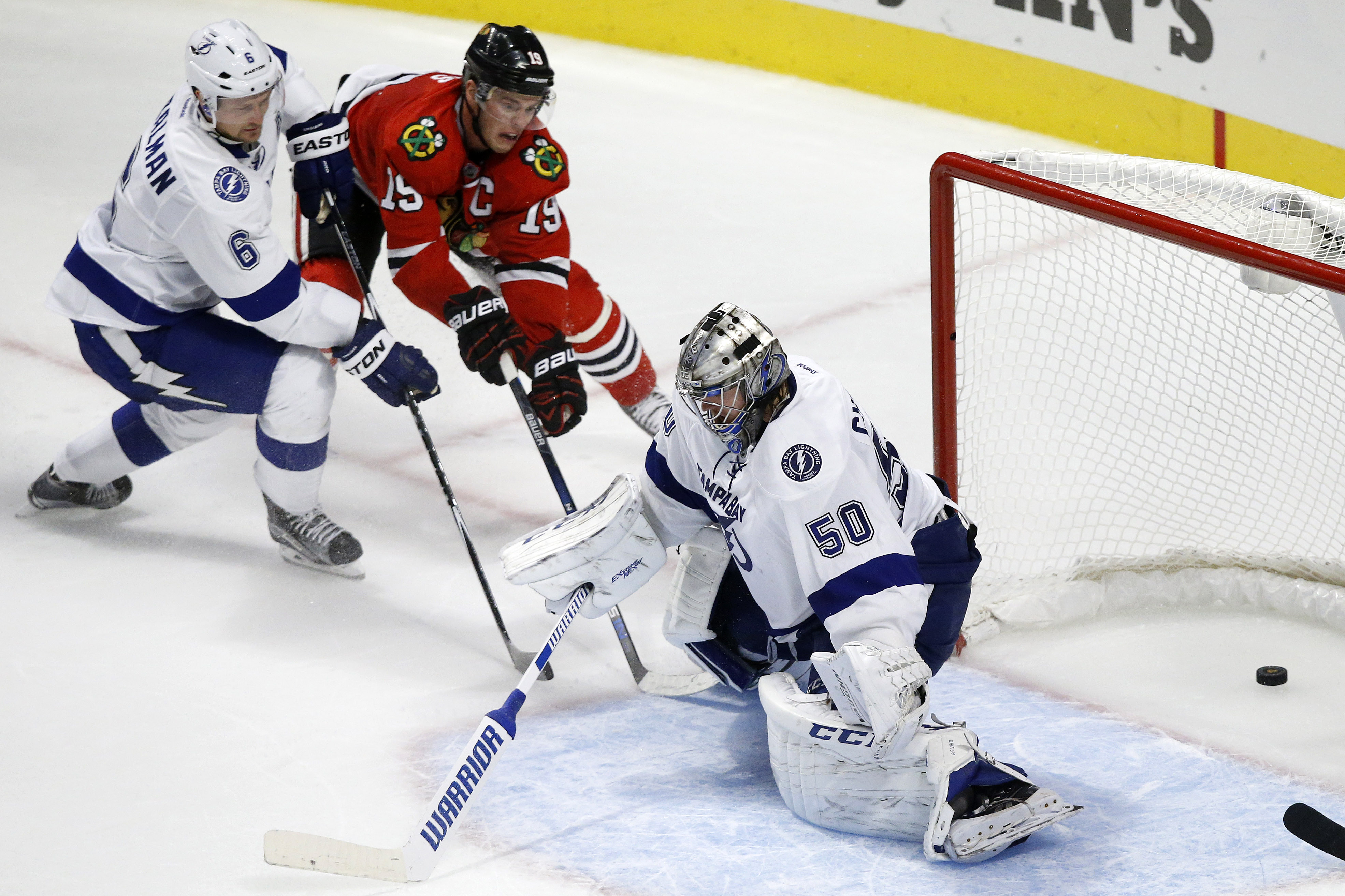 Chicago Blackhawks center Jonathan Toews (19) scores a game winning goal past Tampa Bay Lightning goalie Kristers Gudlevskis and defenseman Anton Stralman (6) during overtime in an NHL hockey game in Chicago, Saturday, Oct. 24, 2015. Chicago won 1-0. (AP