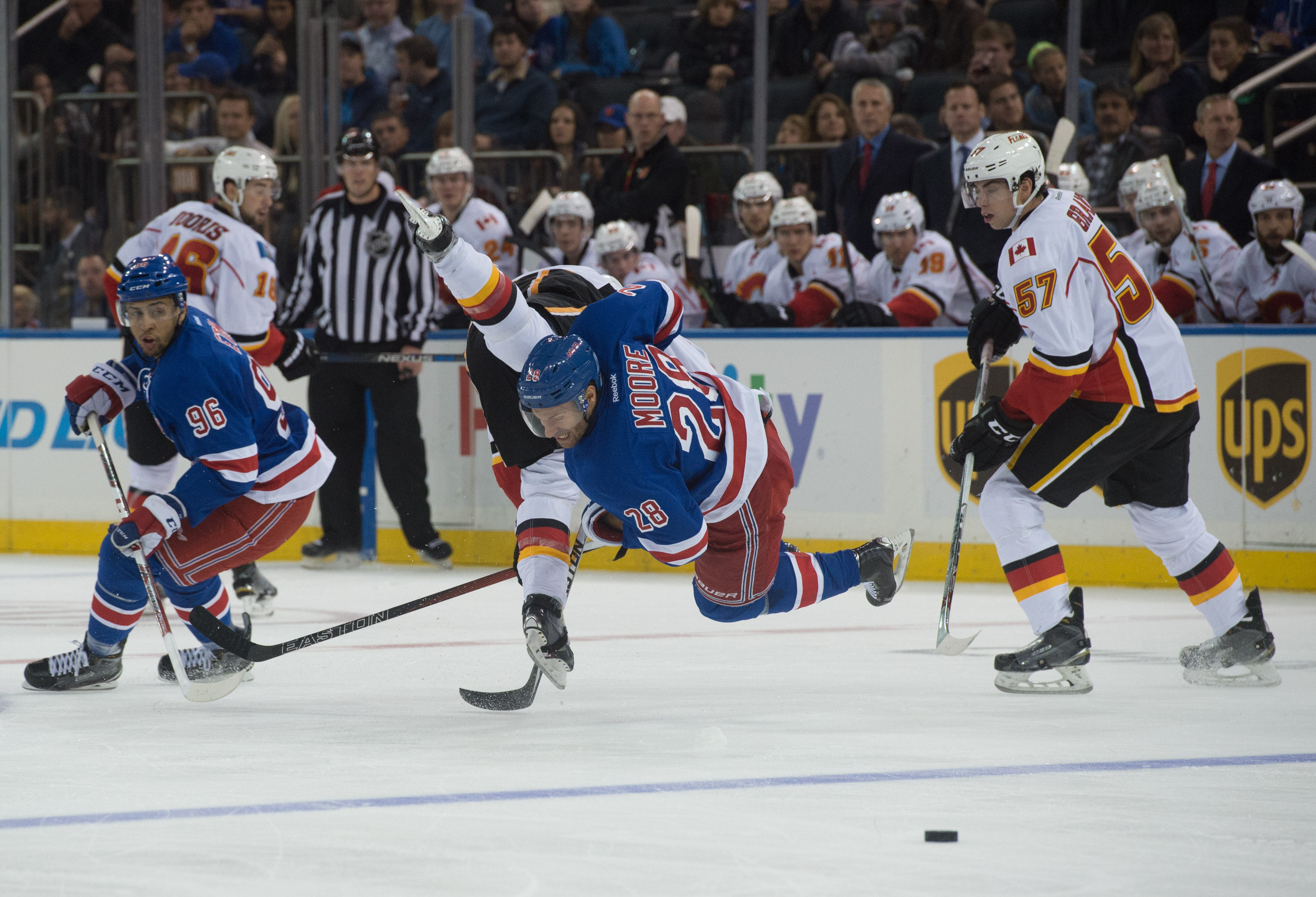 New York Rangers right wing Emerson Etem, left, and Calgary Flames center Derek Grant, right, look on as Flames center Sam Bennett, center left, and New York Rangers center Dominic Moore, center right, collide in the second  period of an NHL hockey game a
