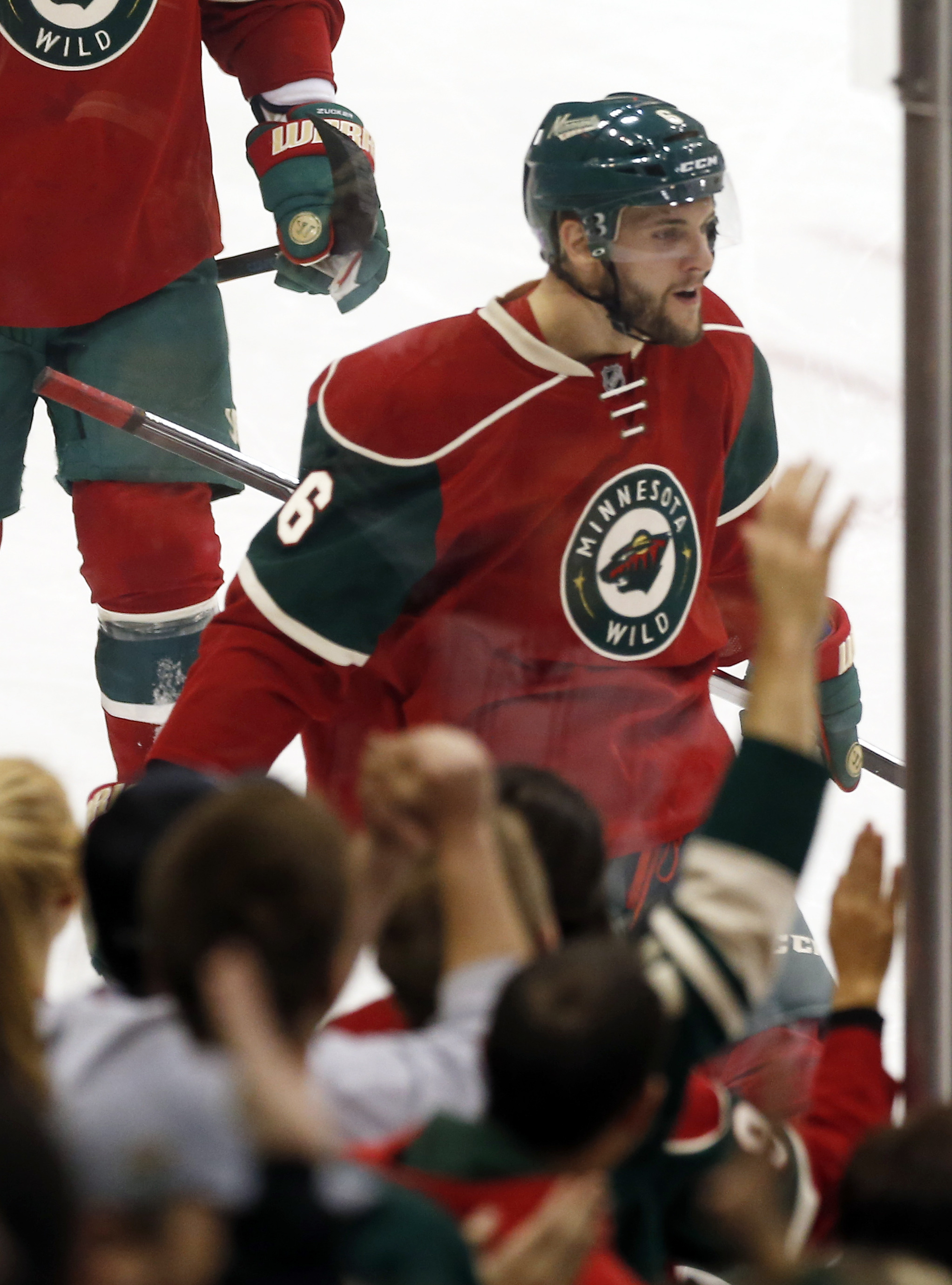 Fans celebrate along with Minnesota Wild's Marco Scandella after his power play goal off Edmonton Oilers goalie Cam Talbot in the first period of an NHL hockey game, Tuesday, Oct. 27, 2015, in St. Paul, Minn. (AP Photo/Jim Mone)