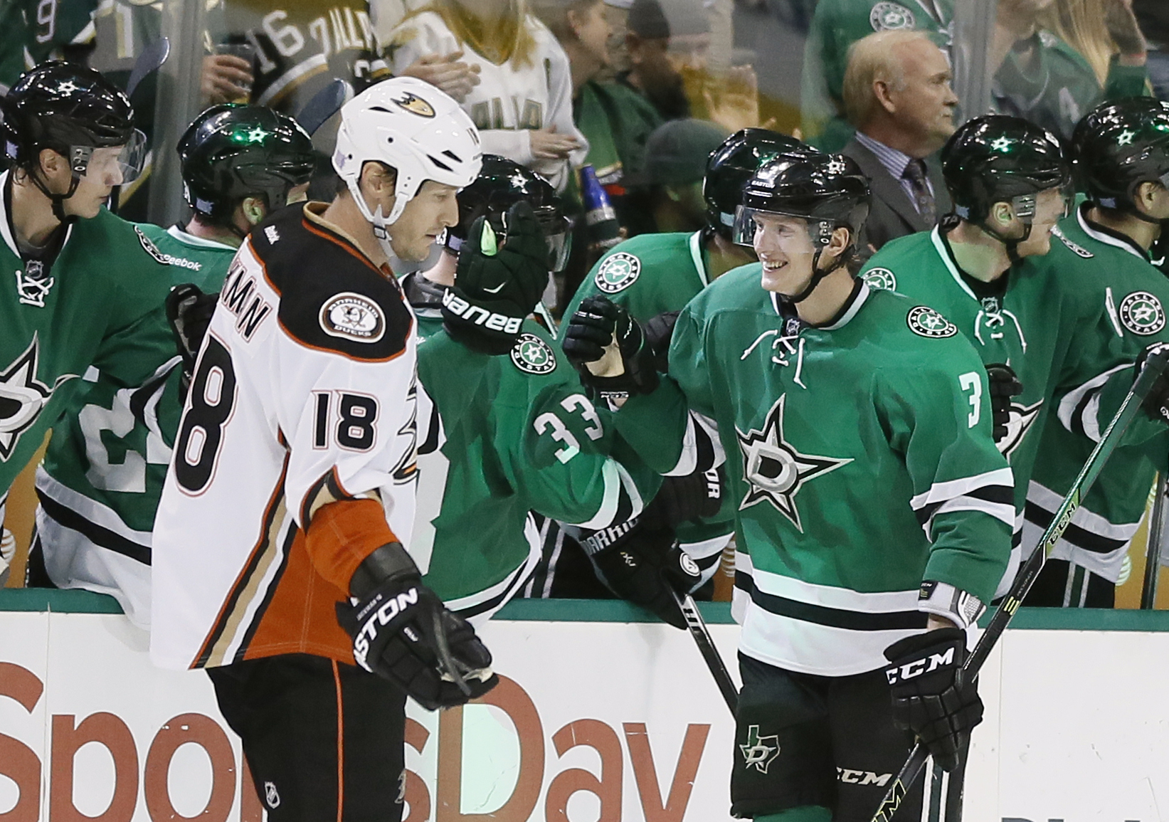 Anaheim Ducks' Tim Jackman (18) skates past Dallas Stars' John Klingberg (3), of Sweden, as Klingberg is congratulated by the bench on his goal against the Ducks in the second period of an NHL hockey game Tuesday, Oct. 27, 2015, in Dallas. (AP Photo/Tony
