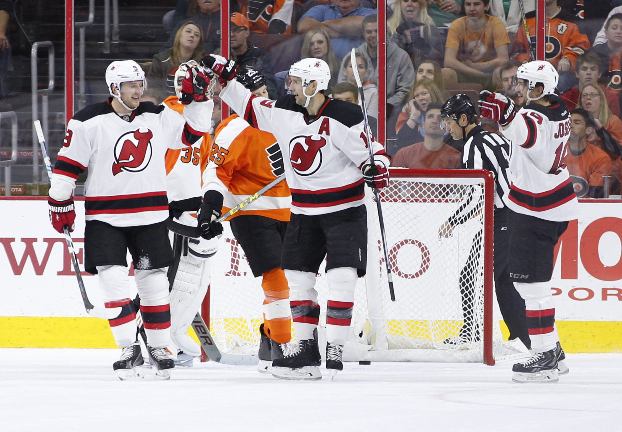 New Jersey Devils' Travis Zajac, center, celebrates his goal on Philadelphia Flyers' Steve Mason, left center, with Jiri Tlusty, left, of Czech Republic and Jacob Josefson, right  during the second period of a hockey game, Thursday, Oct. 29, 2015, in Phil
