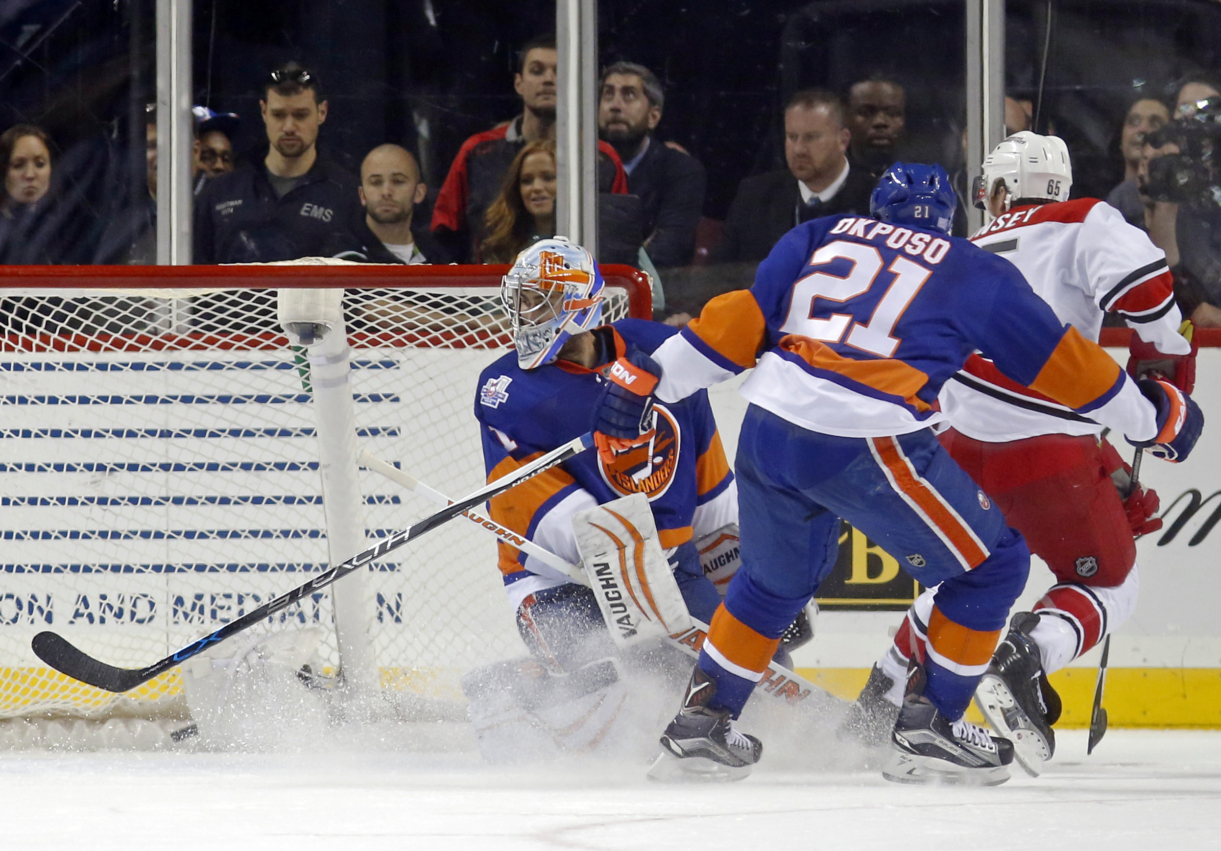 New York Islanders goalie Thomas Greiss (1), of Germany, looks over his shoulder as Carolina Hurricanes defenseman Ron Hainsey (65) scores the winning goal past the defense of Islanders right wing Kyle Okposo (21) in overtime of an NHL hockey game in New
