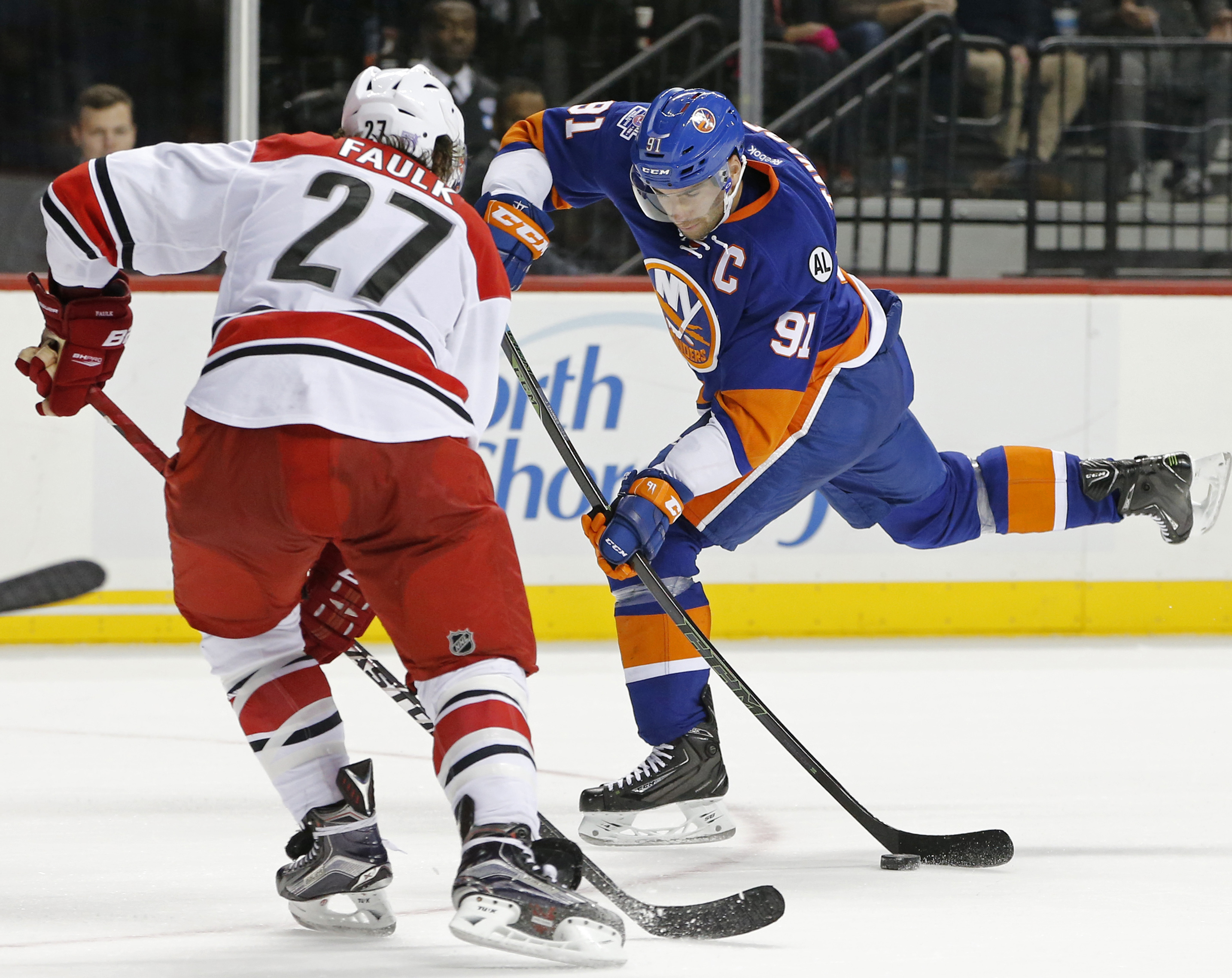 New York Islanders center John Tavares (91) shoots on goal with Carolina Hurricanes defenseman Justin Faulk (27) defending in overtime of an NHL hockey game in New York, Thursday, Oct. 29, 2015. The Hurricanes defeated the Islanders 3-2. (AP Photo/Kathy W
