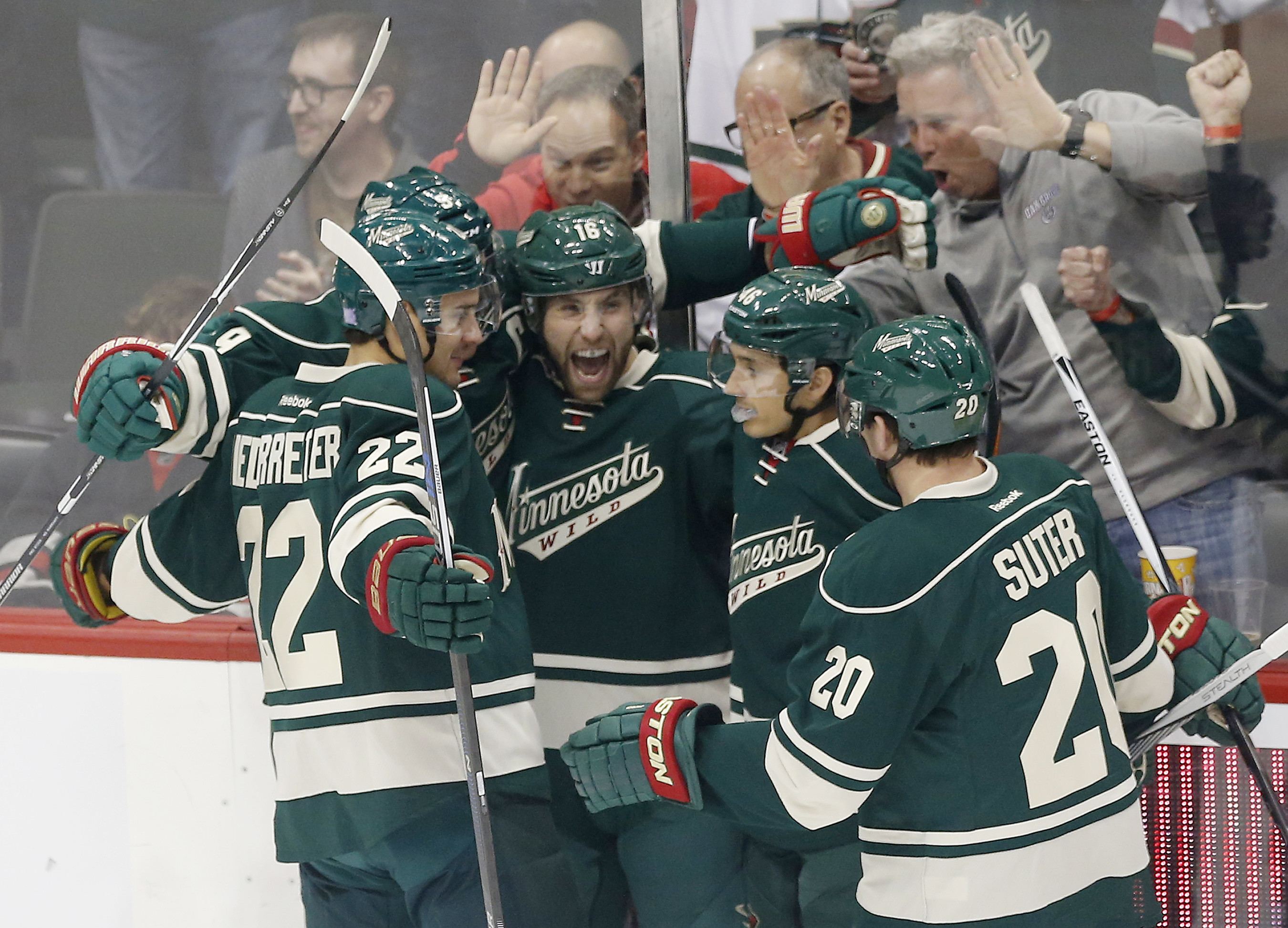 Minnesota Wild's Jason Zucker, second from left, celebrates with teammates after his goal off Chicago Blackhawks goalie Scott Darling in the first period of an NHL hockey game, Friday, Oct. 30, 2015, in St. Paul, Minn. (AP Photo/Jim Mone)